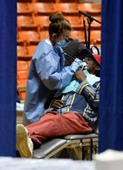 A dental assistant works on a patient during the West Tennessee Mission of Mercy dental clinic, Friday, March 22.