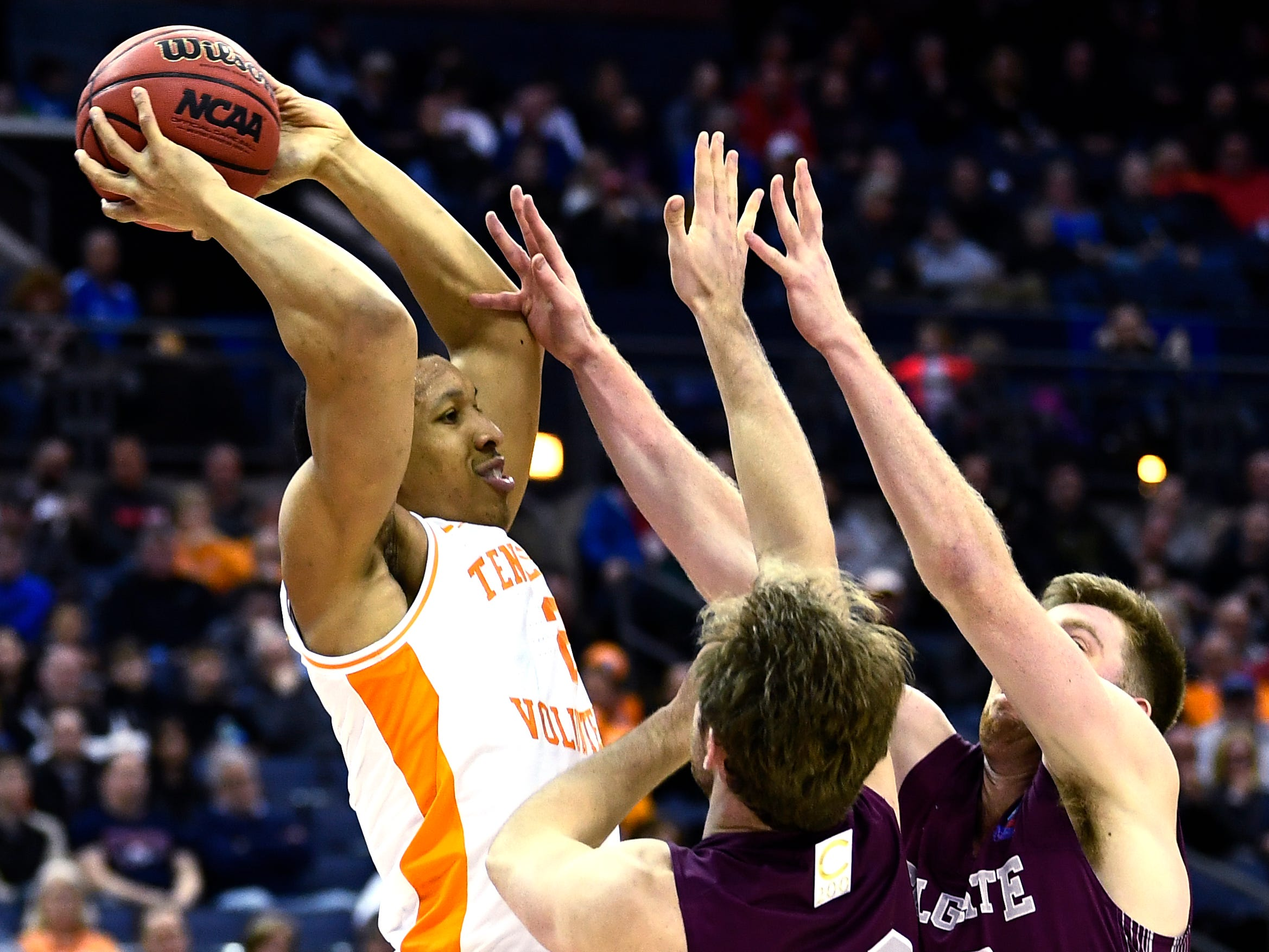 Tennessee forward Grant Williams (2) passes the ball defended by Colgate center Dana Batt (12) and  forward Will Rayman (10) during their first round game in the NCAA Tournament at Nationwide Arena in Columbus, Ohio, on Friday, March 22, 2019.