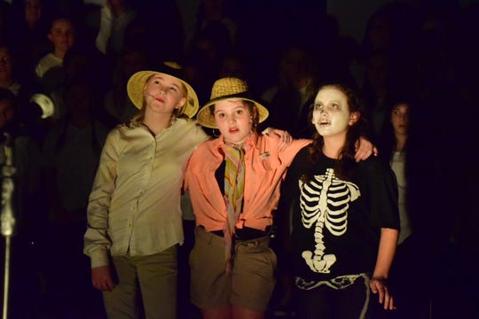 """Charlotte Chrimes as the explorer Taki, Morgan Foley as the explorer Tut, and Maddie Hillis as the skeleton Lucy visit important times through history introducing each scene in Hardin Valley Middle School's sixth-grade musical production, """"Dig it! A Musical Tale of Ancient Civilizations,"""" March 14, 2019."""