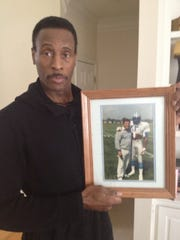 Former University of Tennessee football player Mike Cofer, pictured at his home in Fayetteville, Ga., on March 3, 2013, shows a photograph taken with coach Wayne Fontes during his 10-year NFL career with the Detroit Lions. The Knoxville native has been diagnosed with amyloidosis, a rare disease in which proteins become insoluble and disrupt normal function in the kidneys and other organs.