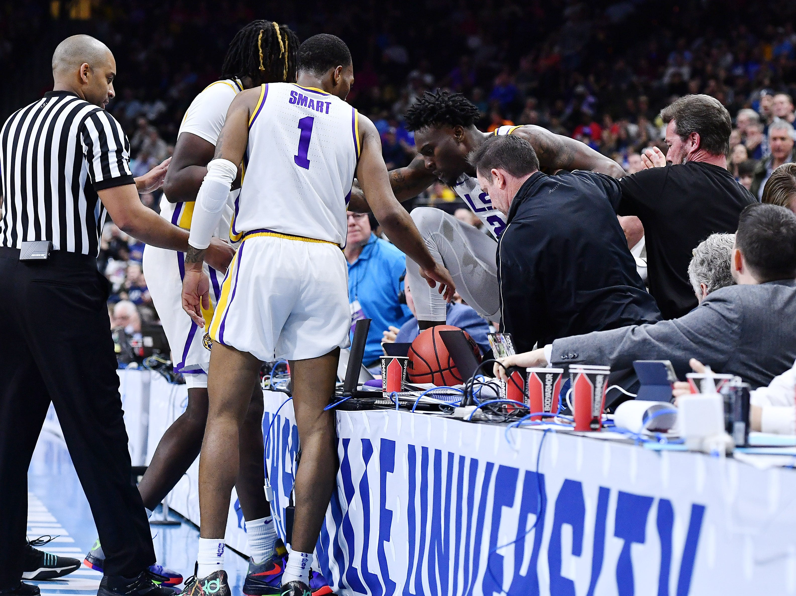 Mar 21, 2019; Jacksonville, FL, USA; LSU Tigers forward Emmitt Williams (24) is helped back on to the court after jumping over the scorers table against the Yale Bulldogs during the second half in the first round of the 2019 NCAA Tournament at Jacksonville Veterans Memorial Arena. Mandatory Credit: John David Mercer-USA TODAY Sports