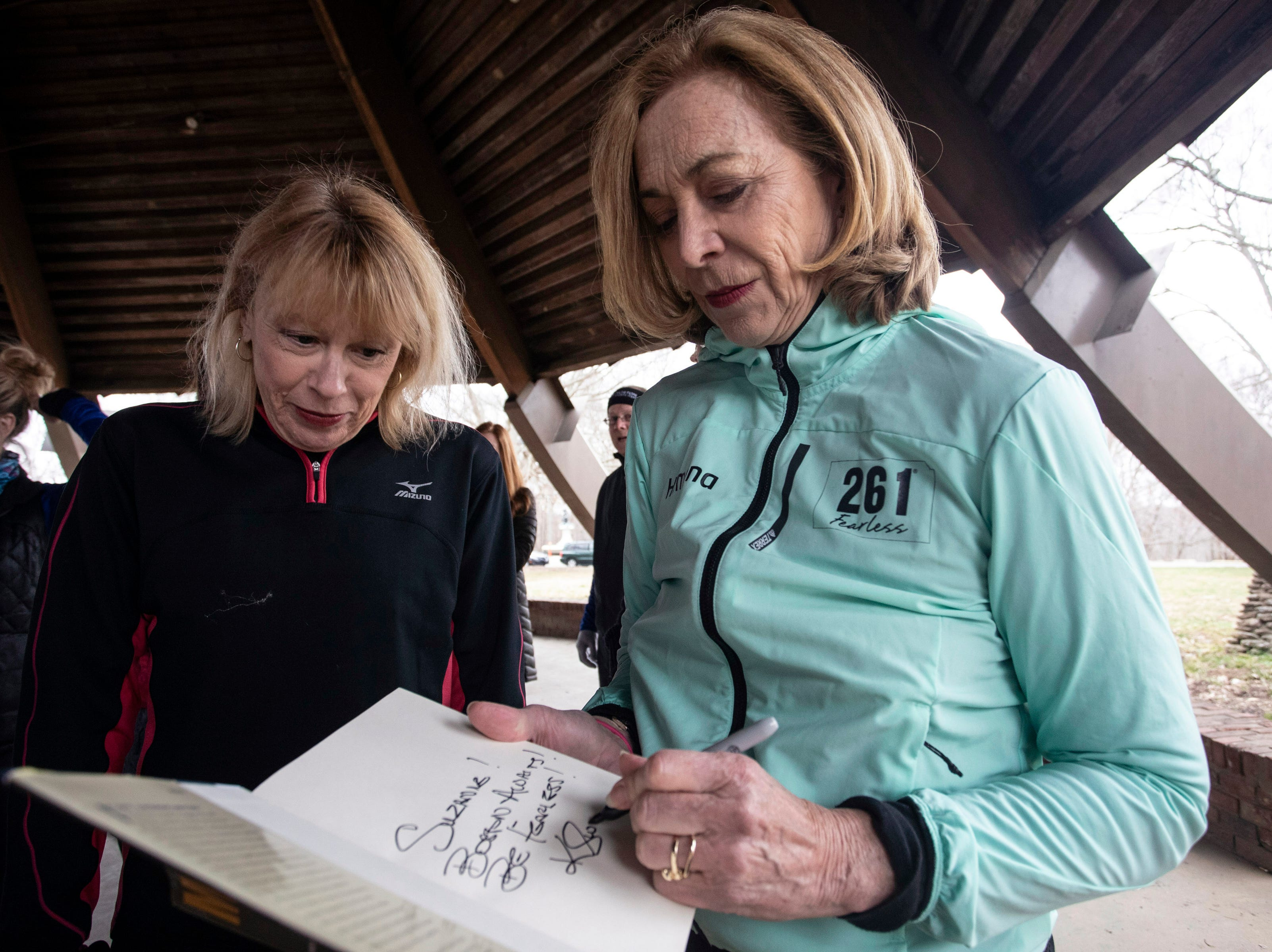 Kathrine Switzer autographed a copy of her book Marathon Woman for Suzanne Duvall during a meet and greet with fellow runners in Cherokee Park on Thursday.