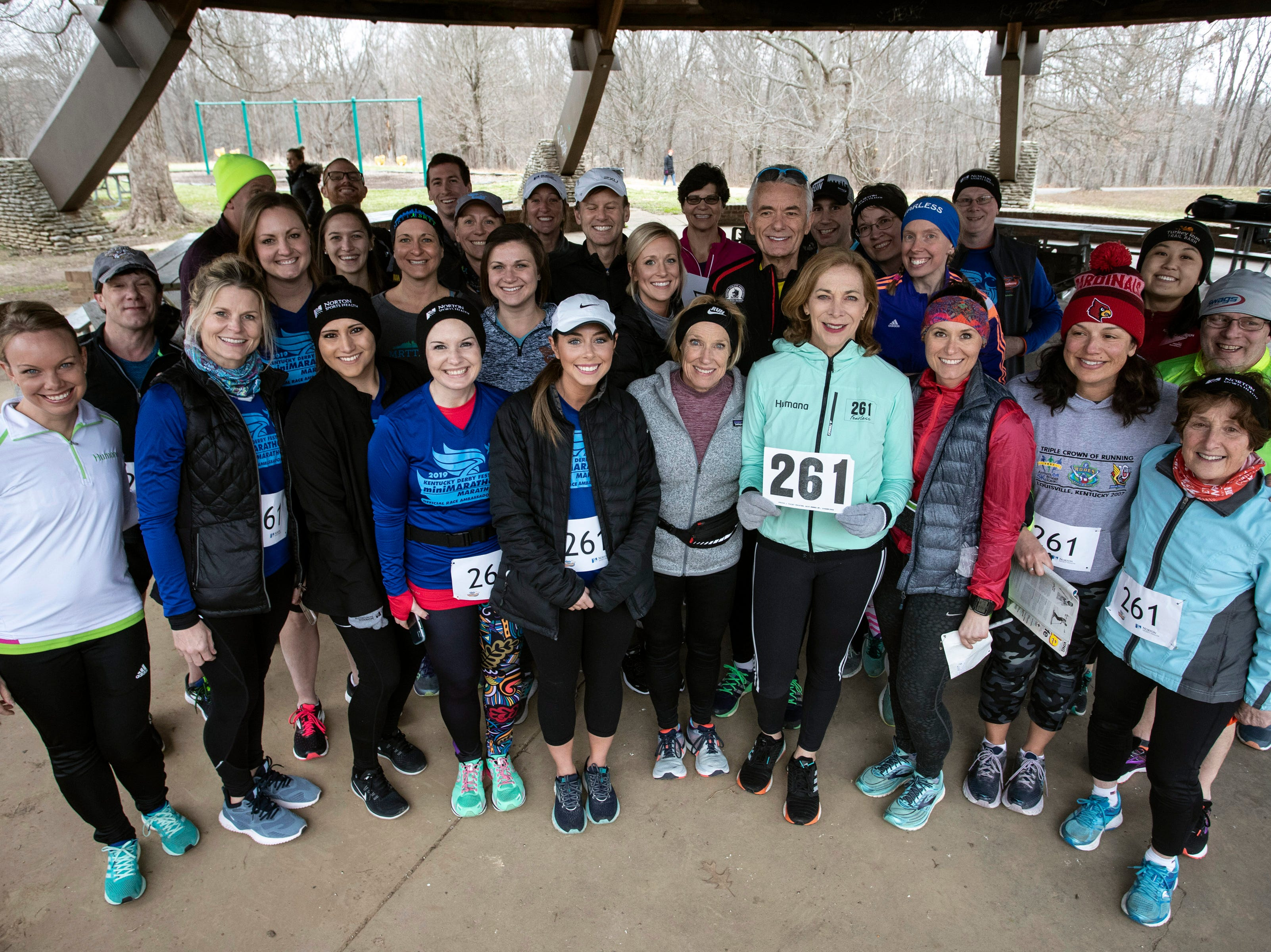 """Holding her famous """"261"""" bib, Kathrine Switzer, who in 1967 became the first woman to run the Boston Marathon as a numbered entrant, posed with a few dozen of her fans near Hogan's Fountain in Cherokee Park on Thursday afternoon. 3/21/19"""