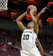Michigan's Deja Church gets fouled on the way to making the bucket by  Kansas State's Kali Jones in the first round of the Women's NCAA Tournament in Louisville on March 22.