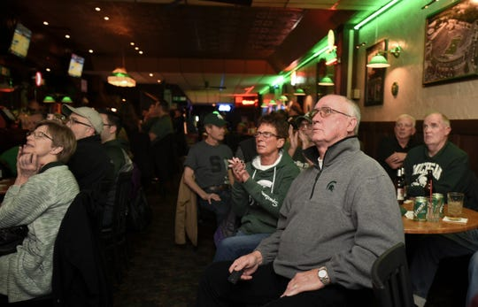 Fred and Debra Wager, middle, former owners of Abie's Bar in downtown Eaton Rapids watch the MSU basketball game, Thursday, March 21, 2019, with fellow patrons.