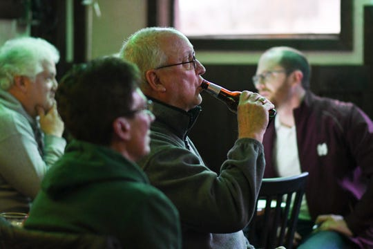 Fred Wager, middle, former owner of Abie's Bar in downtown Eaton Rapids watches the MSU basketball game, Thursday, March 21, 2019, with fellow patrons.  Next to him is his wife Debra.