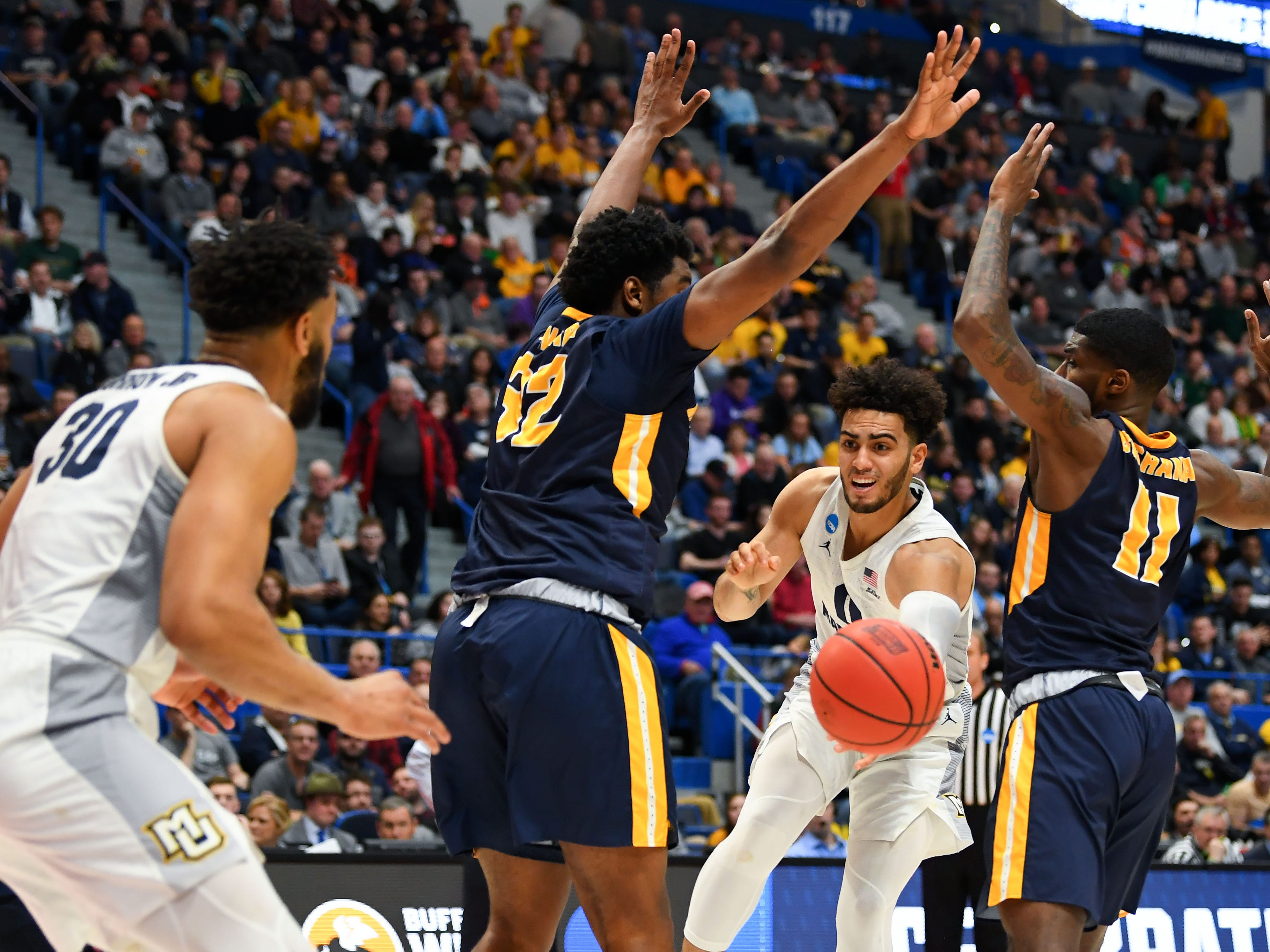 Golden Eagles guard Markus Howard passes the ball to forward Ed Morrow between a pair of Murray State defenders during the first half.