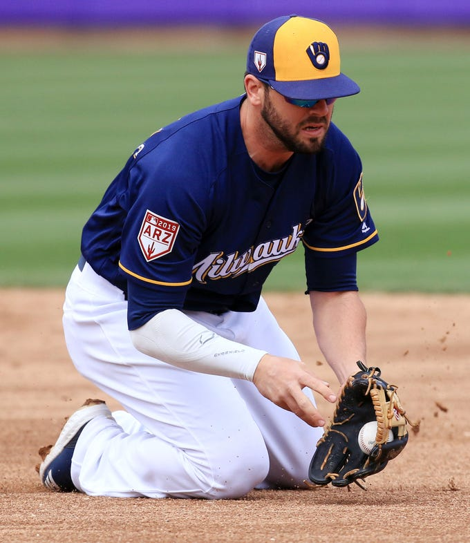 Brewers second baseman Mike Moustakas goes to his knees to field a grounder against the Dodgers on Thursday at American Family Fields of Phoenix.