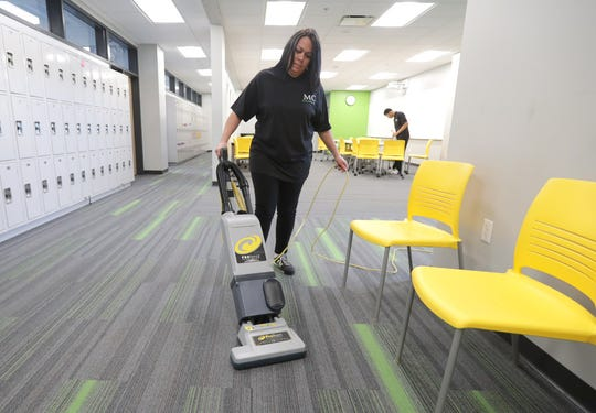MahlerClean service representative Priscilla Castro vacuums as fellow service rep Tercellus Carr wipes down tables after a school day at St. Augustine Academy in Milwaukee.