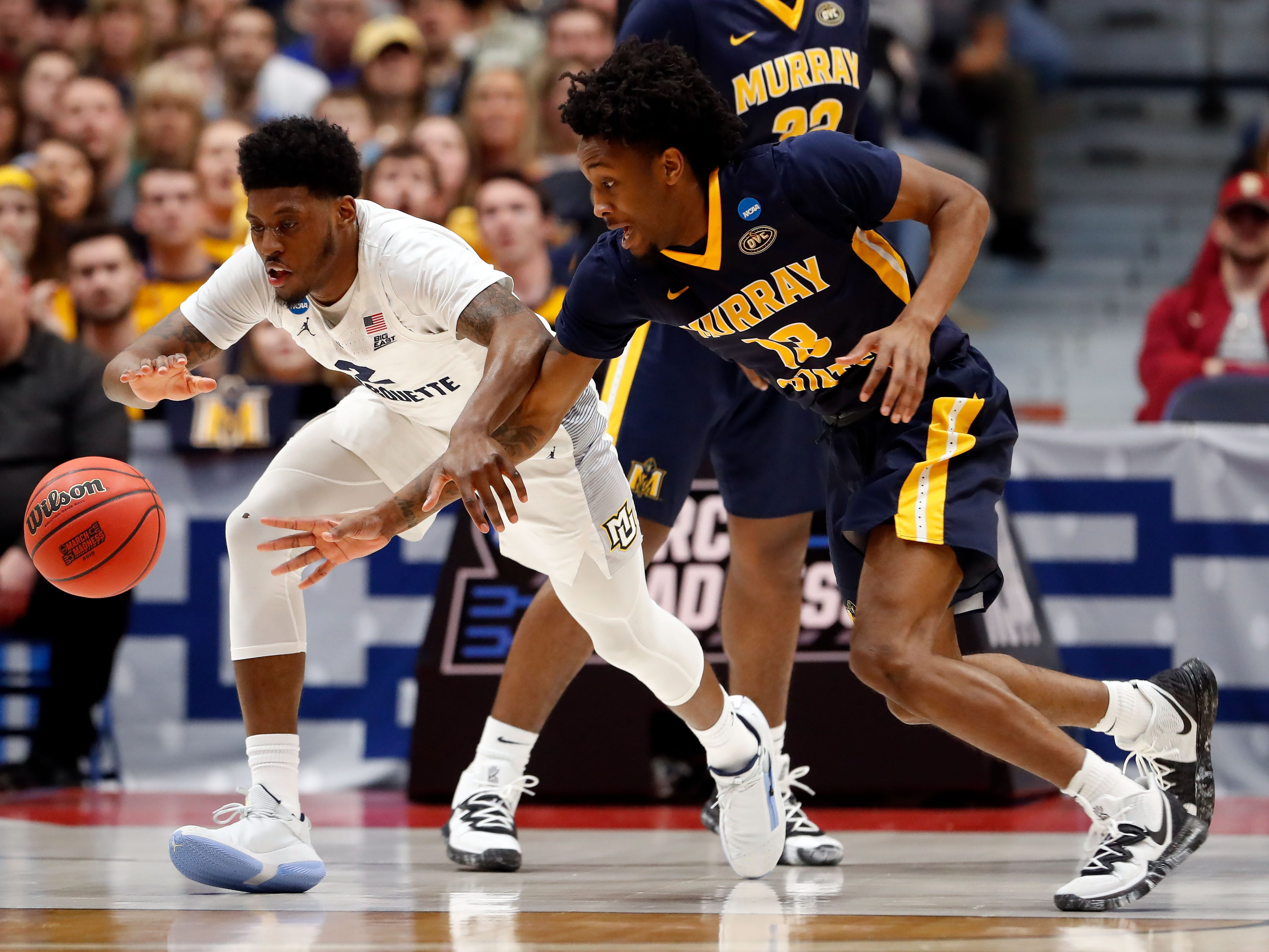 Marquette's Sacar Anim and Devin Gilmore of Murray State chase after a loose ball during the first half.