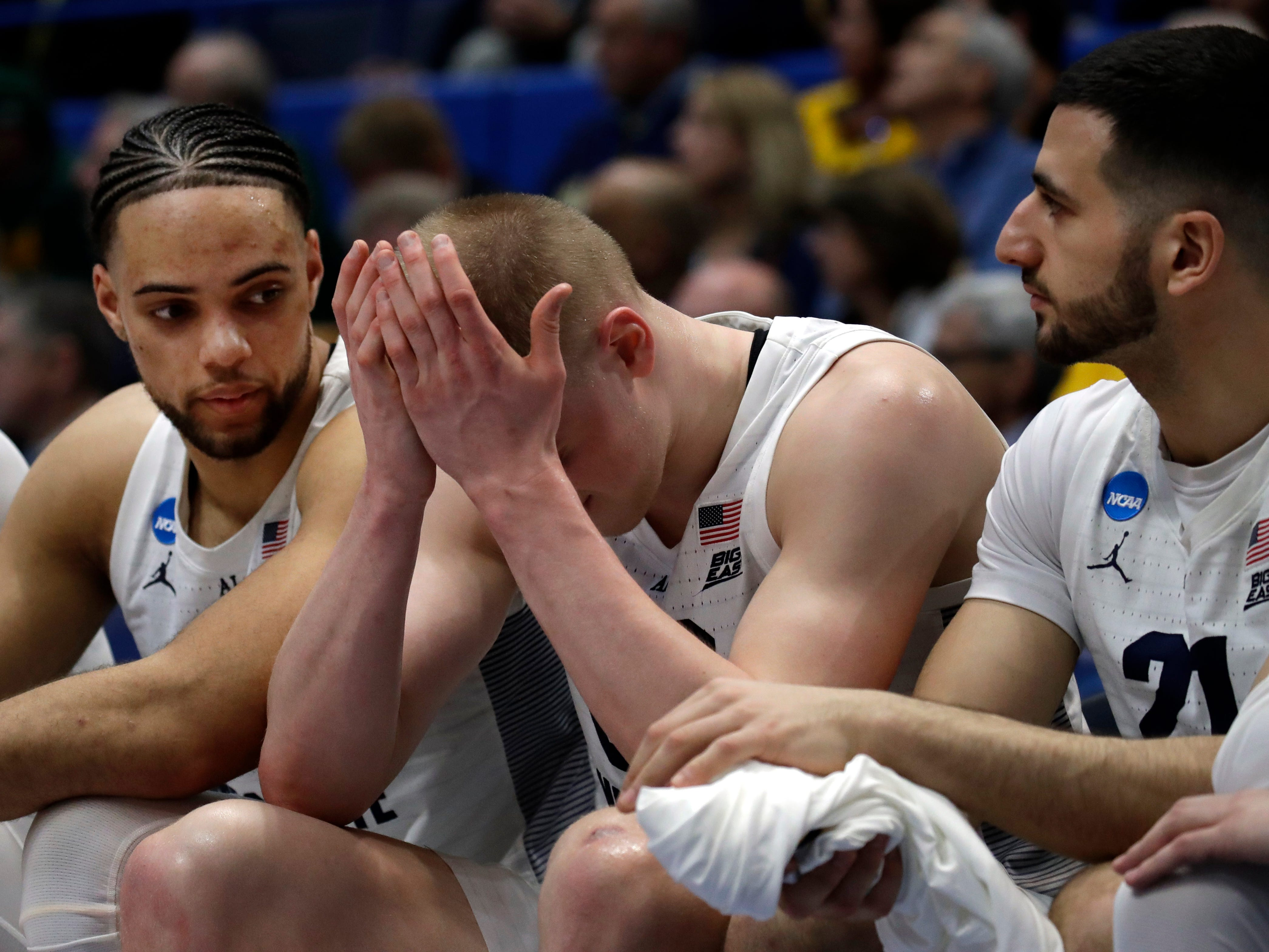 Sam Hauser buries his head in his hands as he sits on the bench for the final seconds of Marquette's loss to Murray State on Thursday in the first round of the NCAA Tournament in Hartford, Conn.