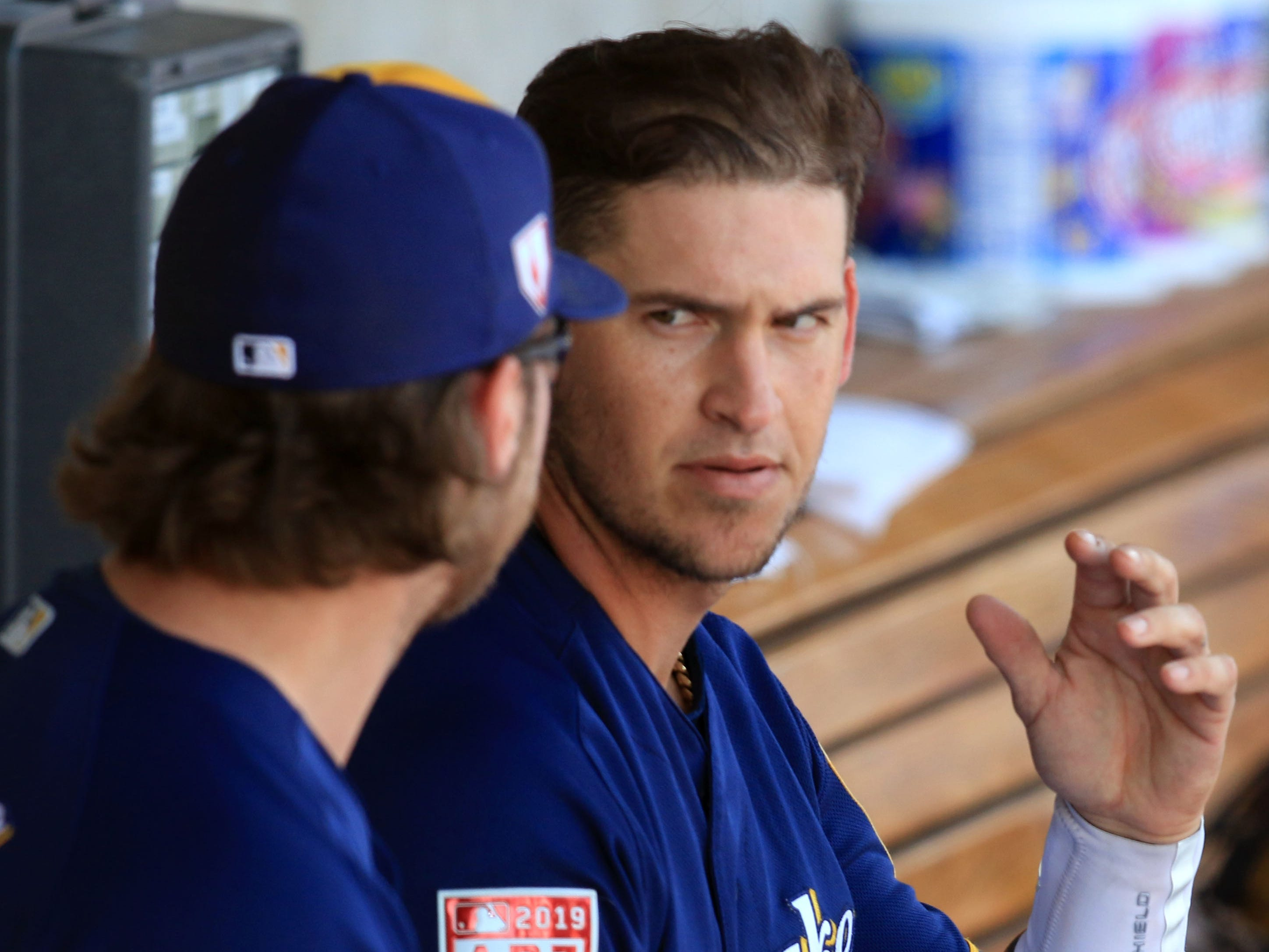 Catcher Yasmani Grandal (right) and starting pitcher Corbin Burnes chat in the Brewers dugout between innings Thursday.