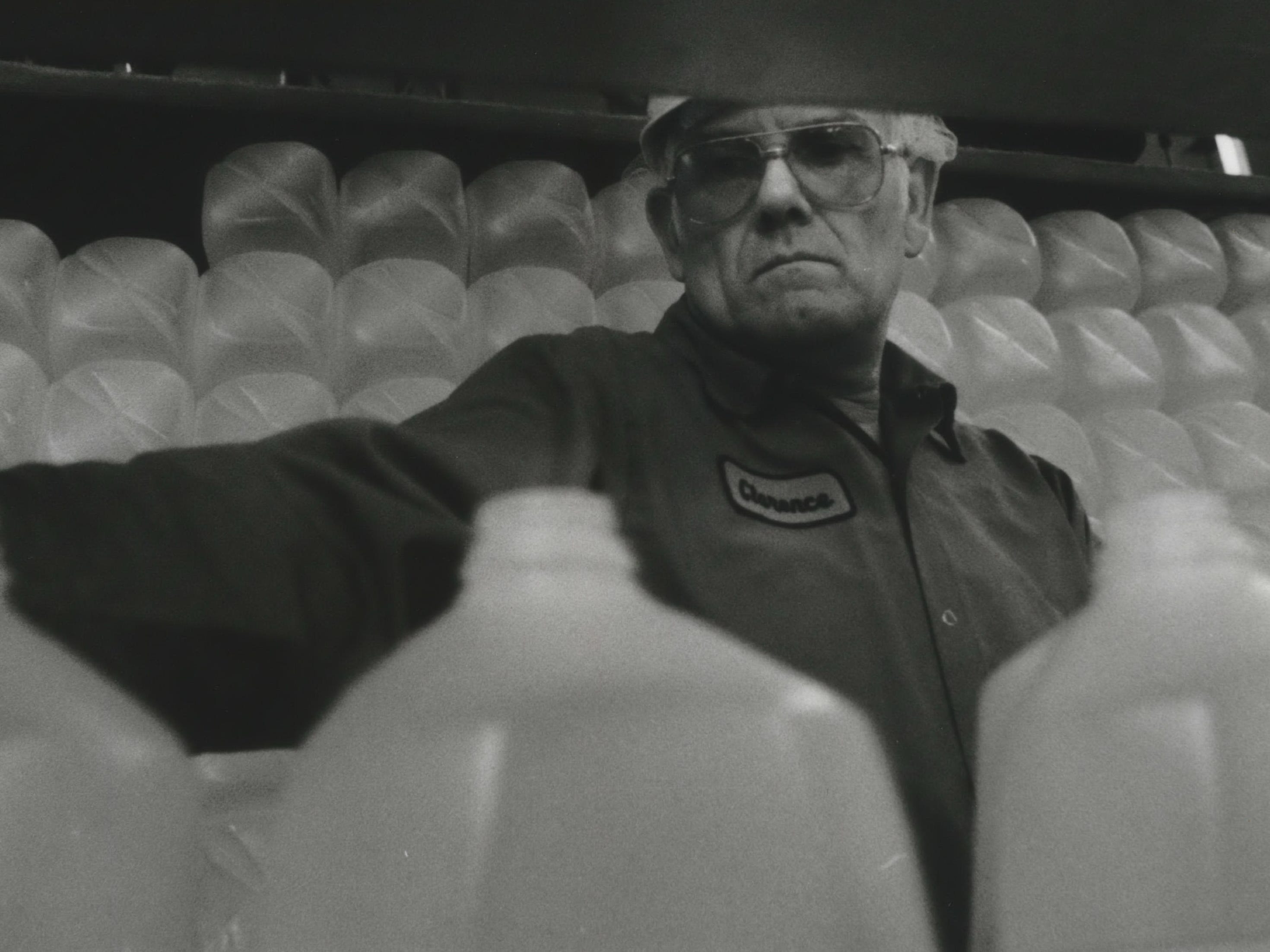 Clarence Gerbig plucks plastic bottles off a conveyor belt at Golden Guernsey Dairy in Waukesha. The dairy manufactures gallon and half-gallon bottles. Excess bottles are picked up by Kohl's Foods Stores and Pick n' Save Stores for customers to use when they buy water.