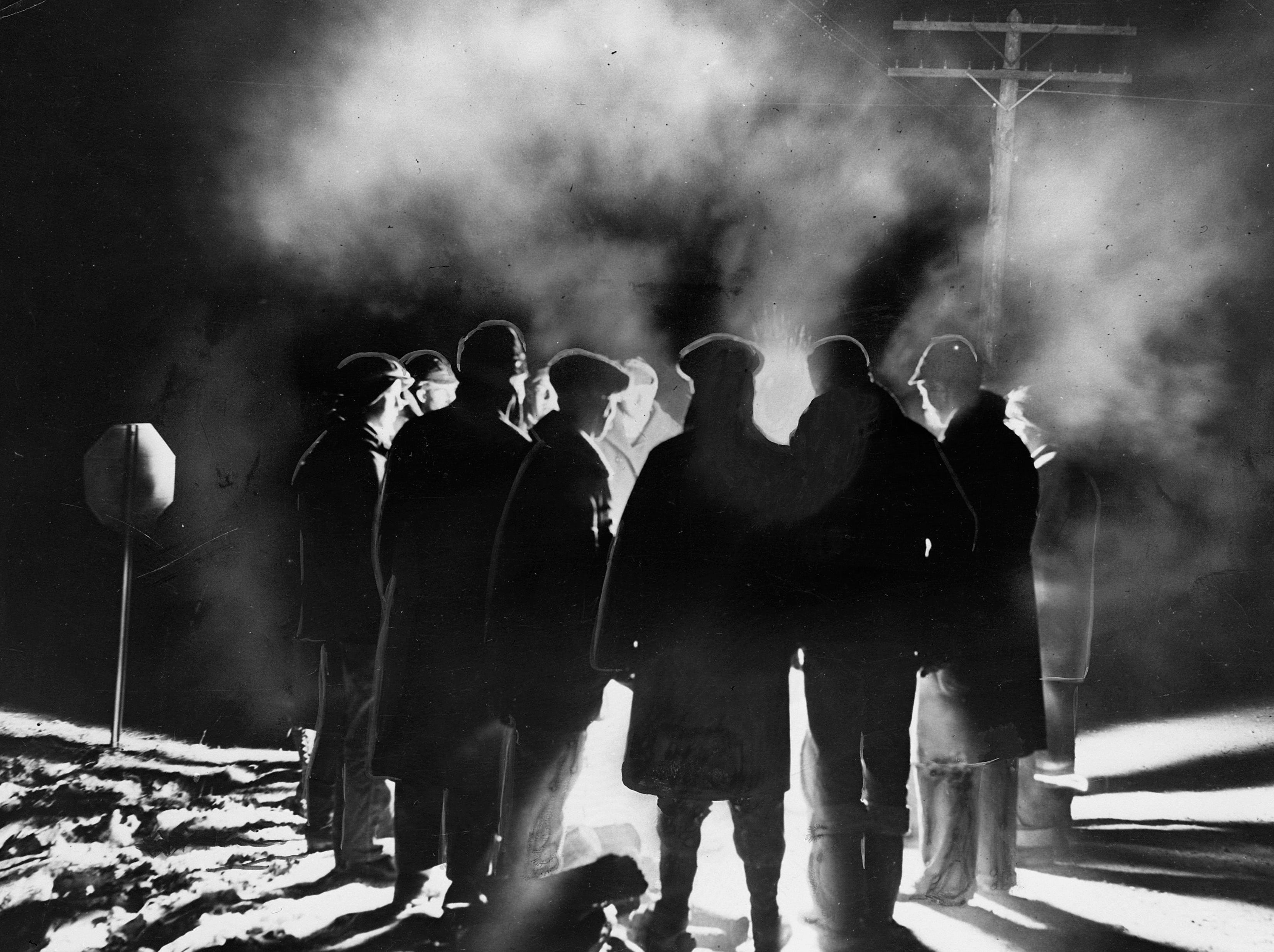 1933: A group of Wisconsin dairy farmers upset with the falling price of milk and their declining percentage of  revenue during the Great Depression spent the night picketing. The farmers are shown on Highway 26 north of New London as they huddled around a fire.