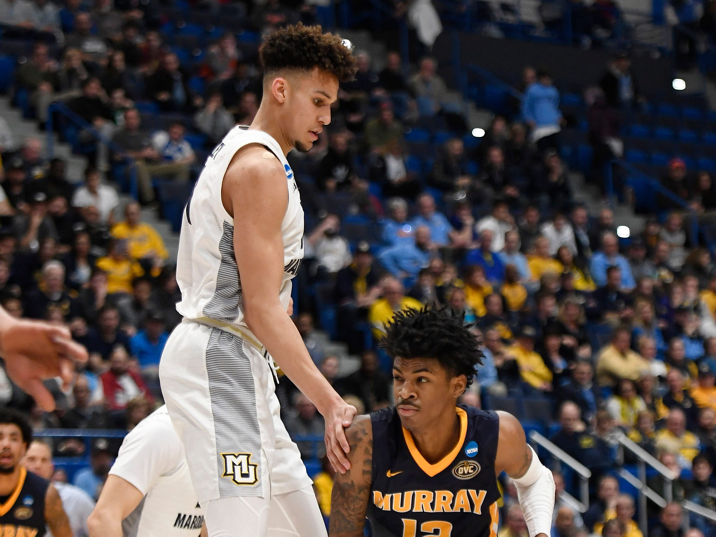 Murray State's Ja Morant drives around Marquette's Brendan Bailey after getting the forward in the air with a pump fake.