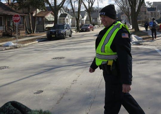 West Allis Police Officer Darrin Kmichik worked as a crossing guard Monday, March 18, near Woodrow Wilson Elementary School in West Allis.