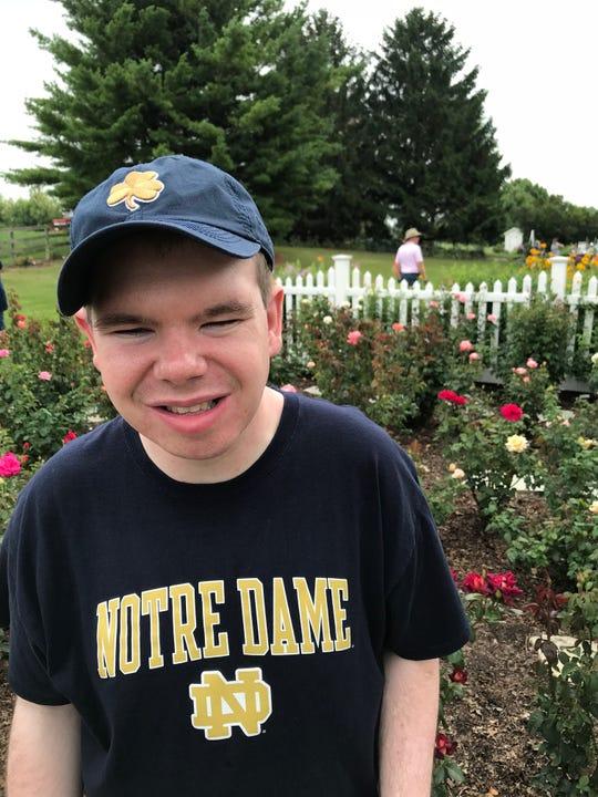 Karen Franco's son, Jacob, poses near a friend's rose garden.