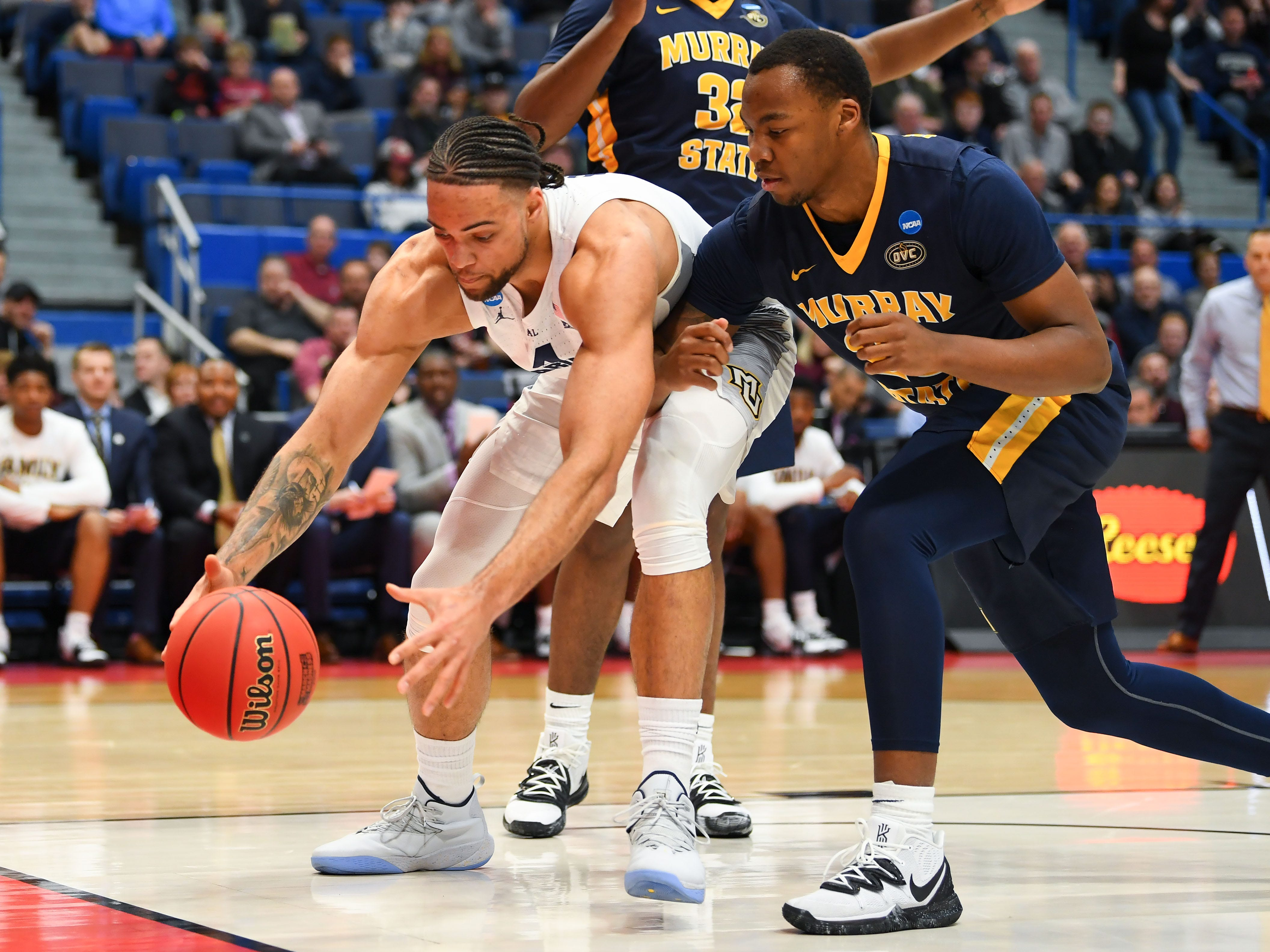 Golden Eagles forward Theo John tries hold off Murray State's KJ Williams while corralling a loose ball before it goes out of bounds during the first half.