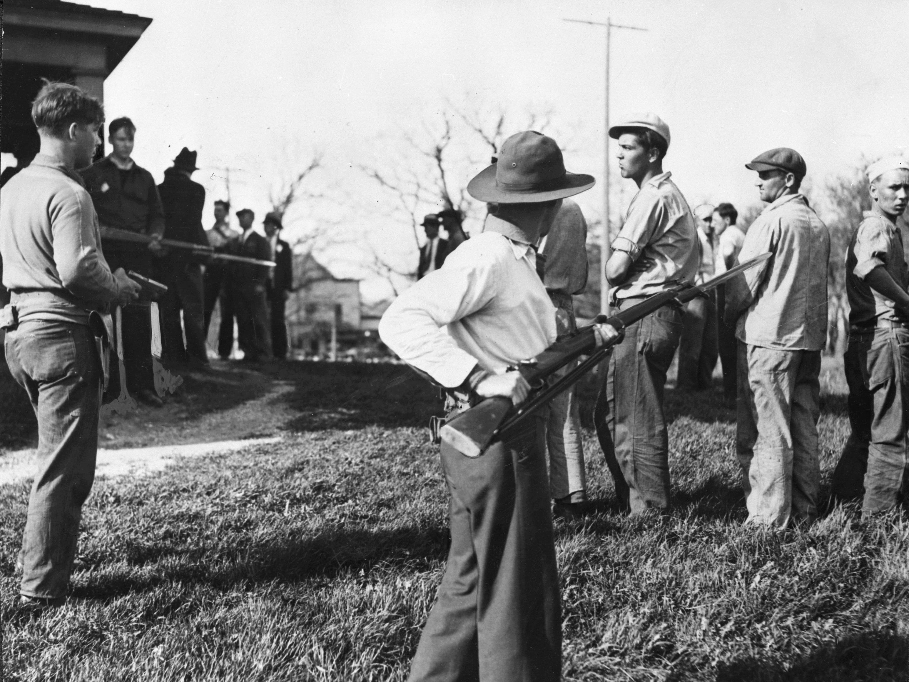 1933: A group of milk strike pickets are held at bay after being taken out of a farmhouse near Durham Hill.