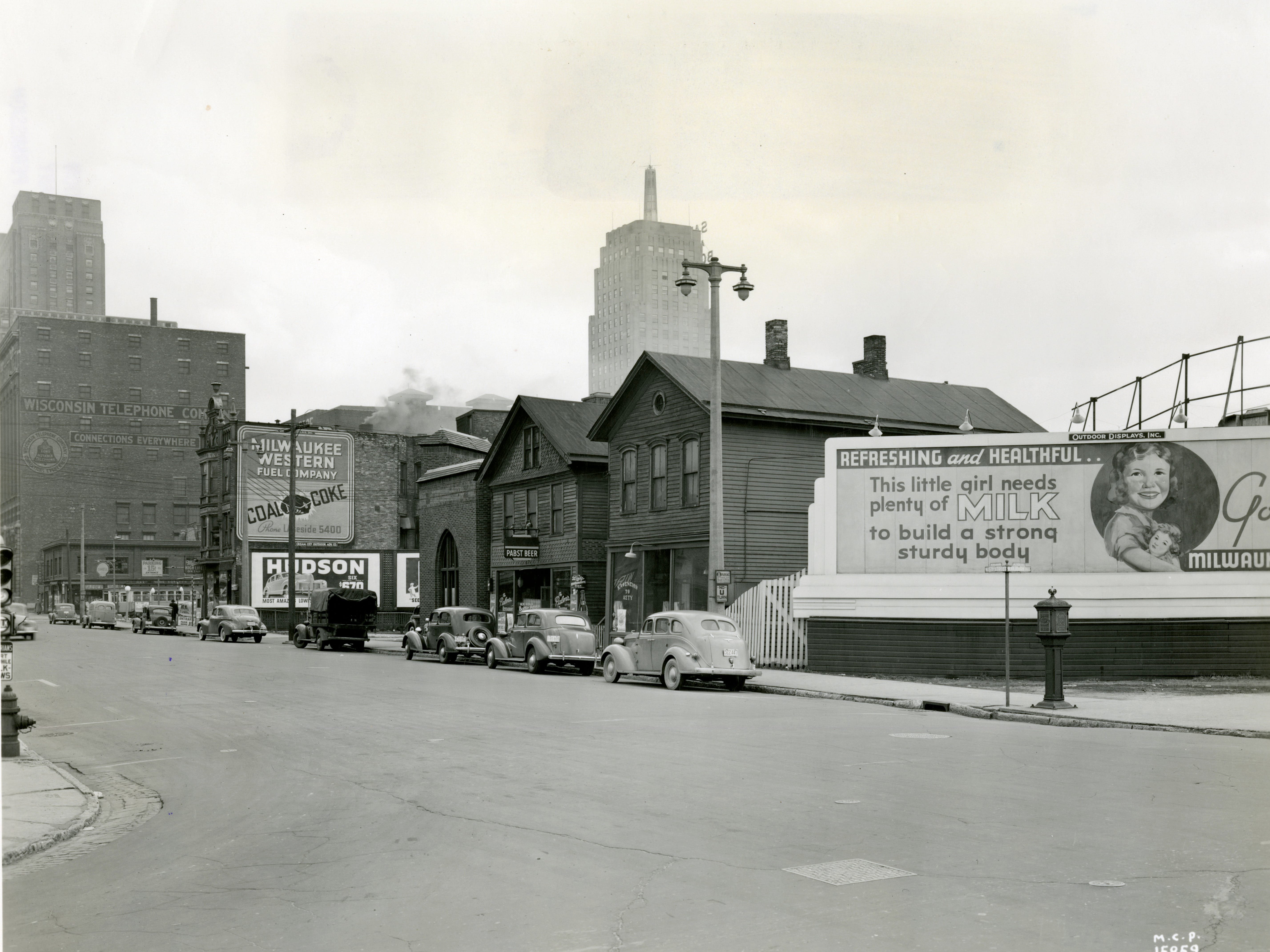 By 1940, fortunes were again turning for the dairy industry. Billboards like this one near 5th Street and Wisconsin Avenue touted the importance of milk to a child's growth and development.