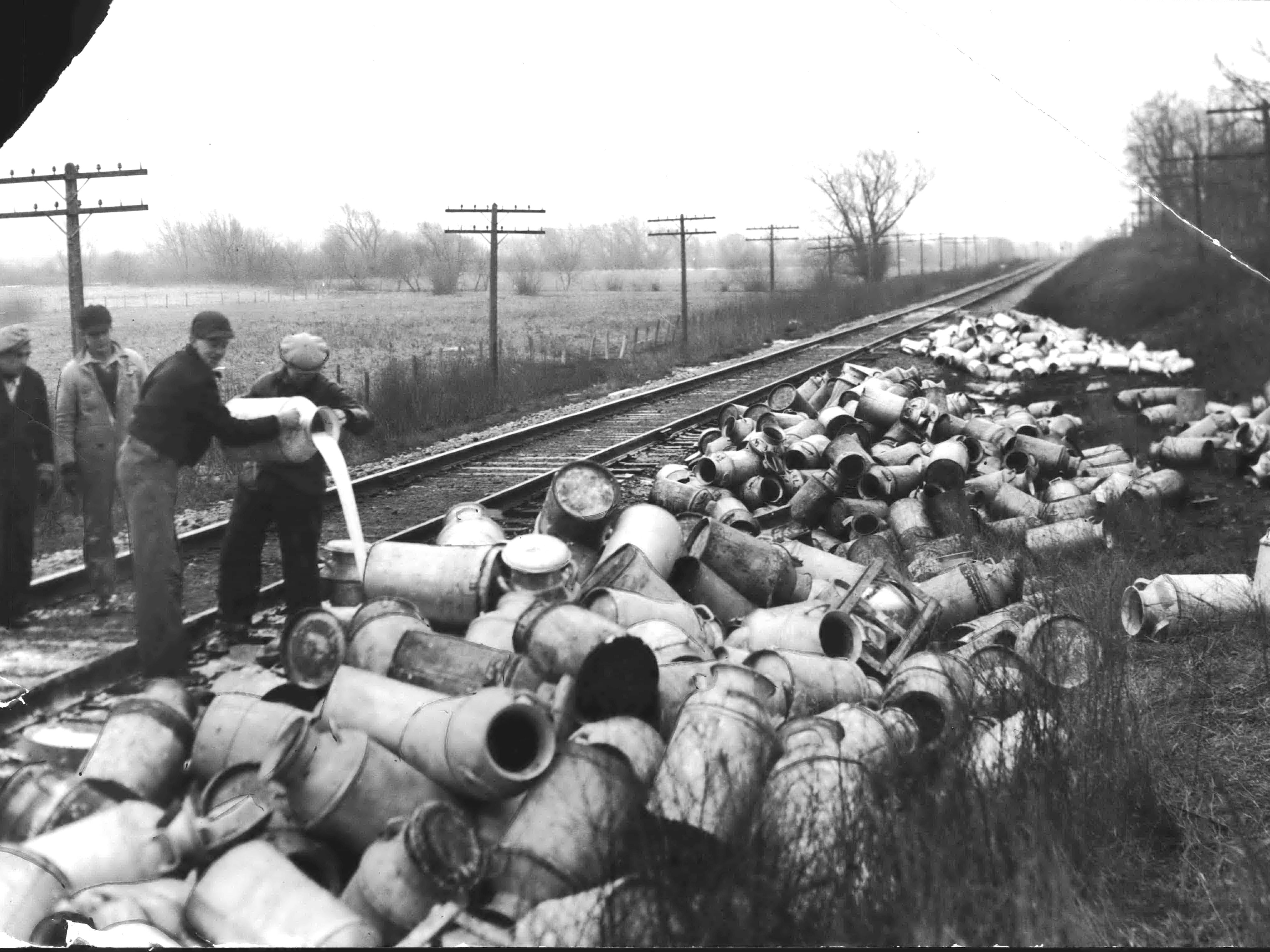 As the Great Depression took hold in the late 1920s, many farmers saw their milk prices drop and by 1933, prices were less than half what they had been just three years prior. Farmers reacted with milk strikes, and the protests often turned violent. This is the scene after a crowd of pickets stopped a Soo Line freight train near the city limits of Burlington by throwing ties across the tracks and firing shots. The pickets broke open seven cars and dumped the cans of milk along the tracks.