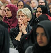 People listen to the names of the victims of the New Zealand mosque attacks being read aloud at a vigil Thursday night at the Islamic Society of Milwaukee's Community Center.