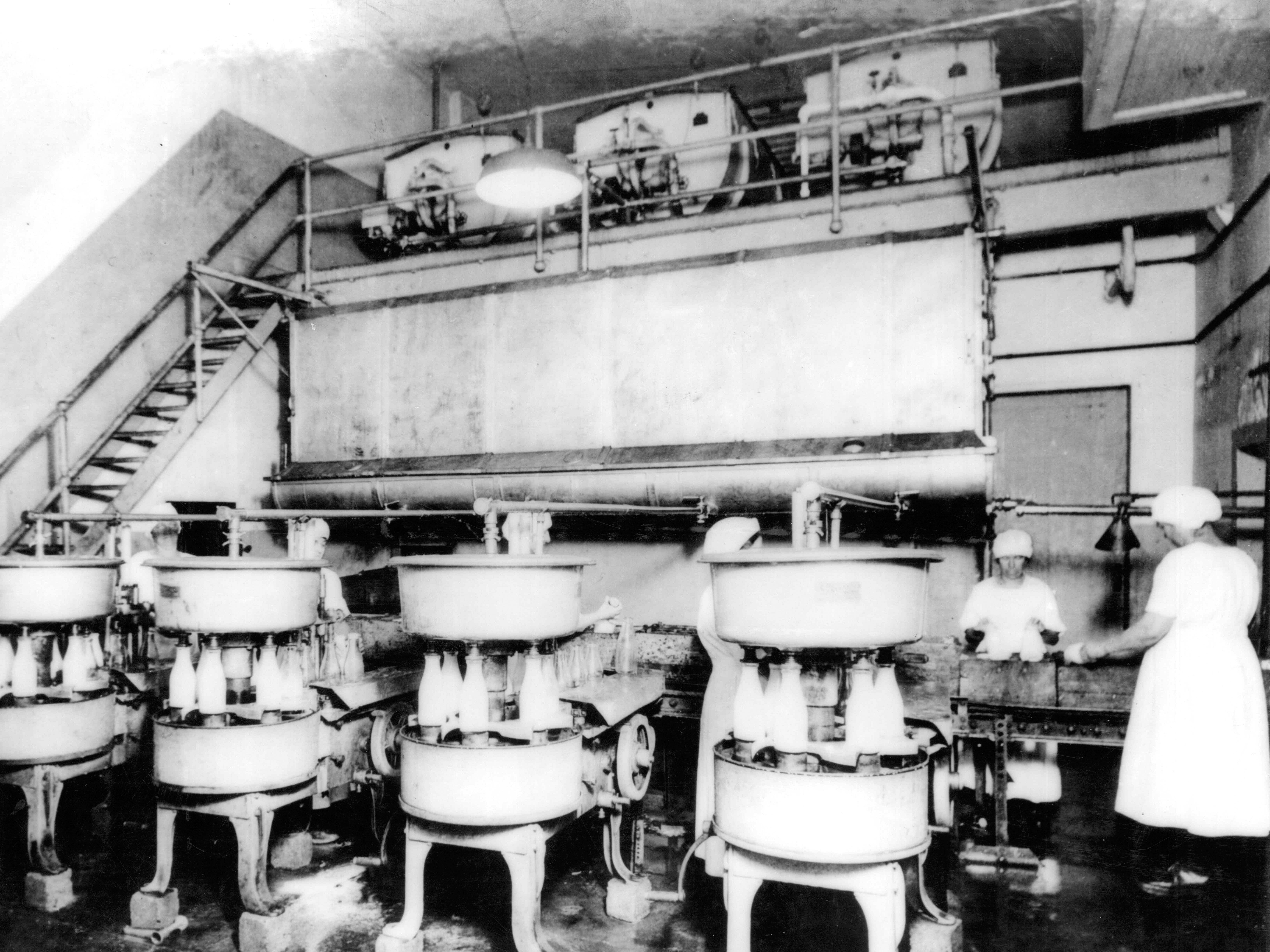 In 1884, the first glass milk bottles were patented. Two years later, the automatic bottle filler and capper joined the production lines. Two female employees of the Waukesha Milk Co. are shown working alongside four bottling machines (circa 1915).