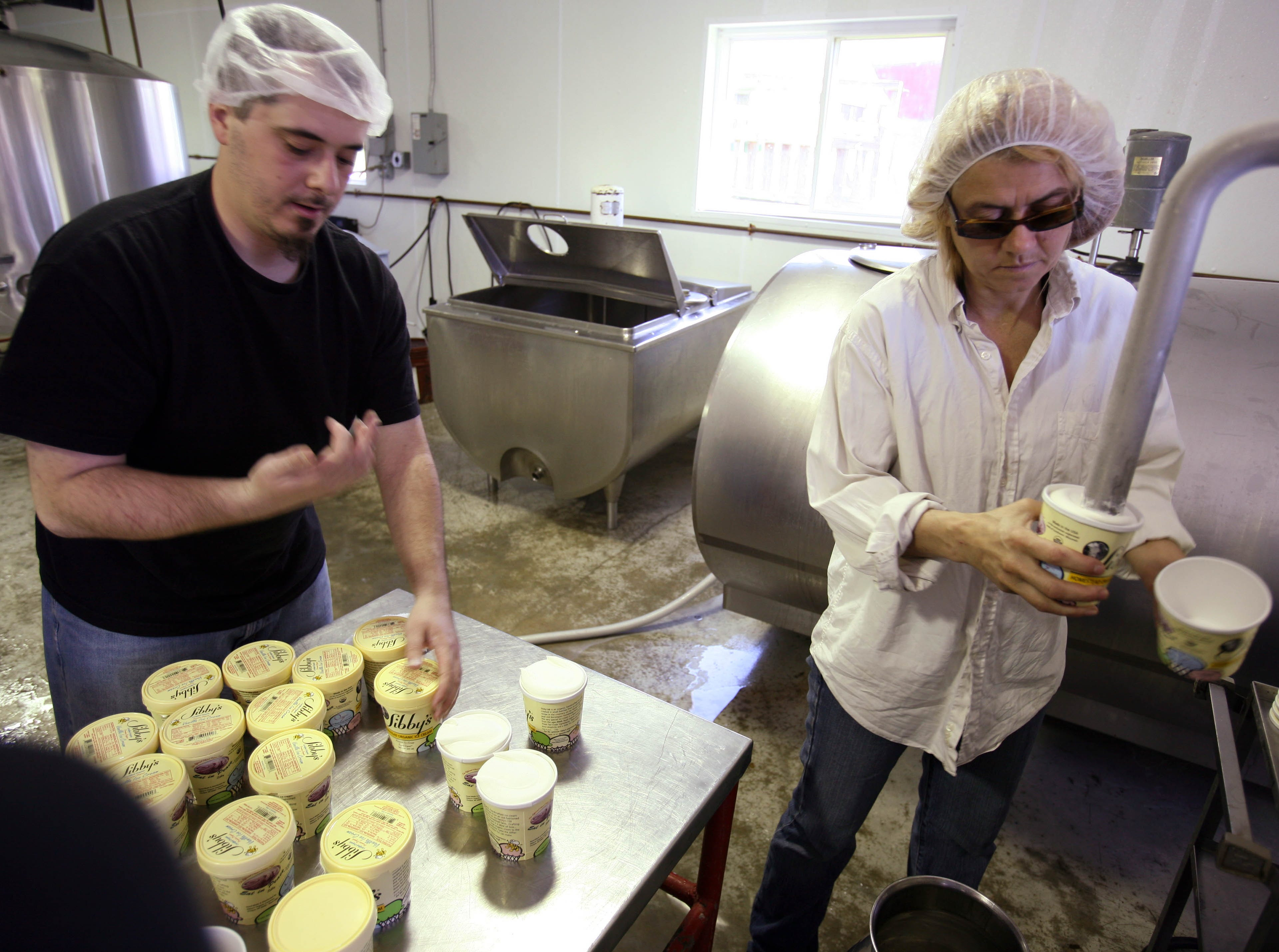 2008: Milk production has been leveraging another revenue stream through the growth of organic products. Sue Sebion (right) filled some of the 3,200 pints of vanilla ice cream while employee William Asad put on covers at Sibby's Premium Organic Ice Cream near Viroquas. The organic ice cream custard product is handmade from fresh, local milk.