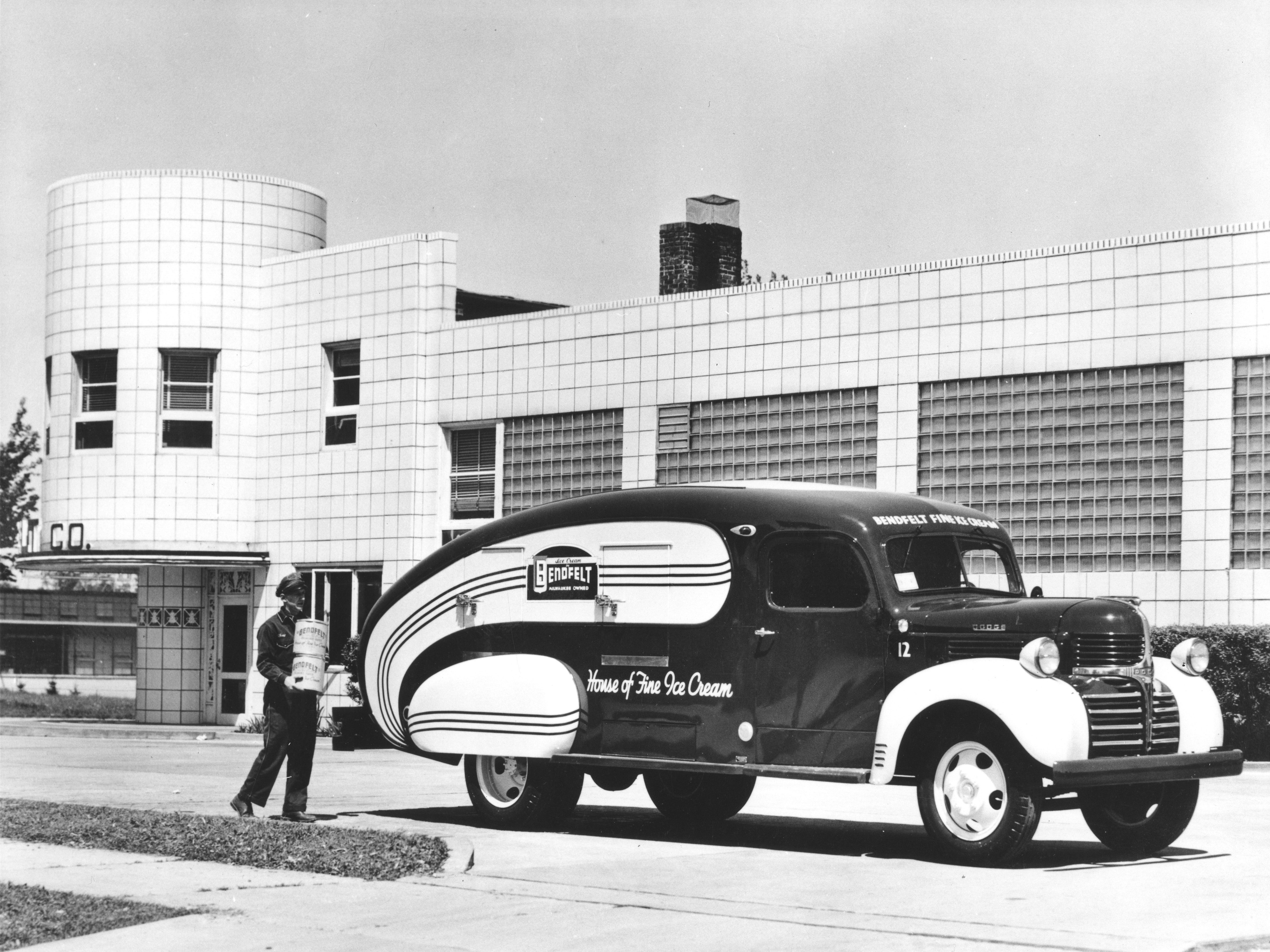 1935: A uniformed man carries two containers of ice cream to a vintage Bendfelt Ice Cream refrigerated truck. Bendfelt started in 1917 when Walter H. Bendfelt took over the Standard Ice Cream Co.