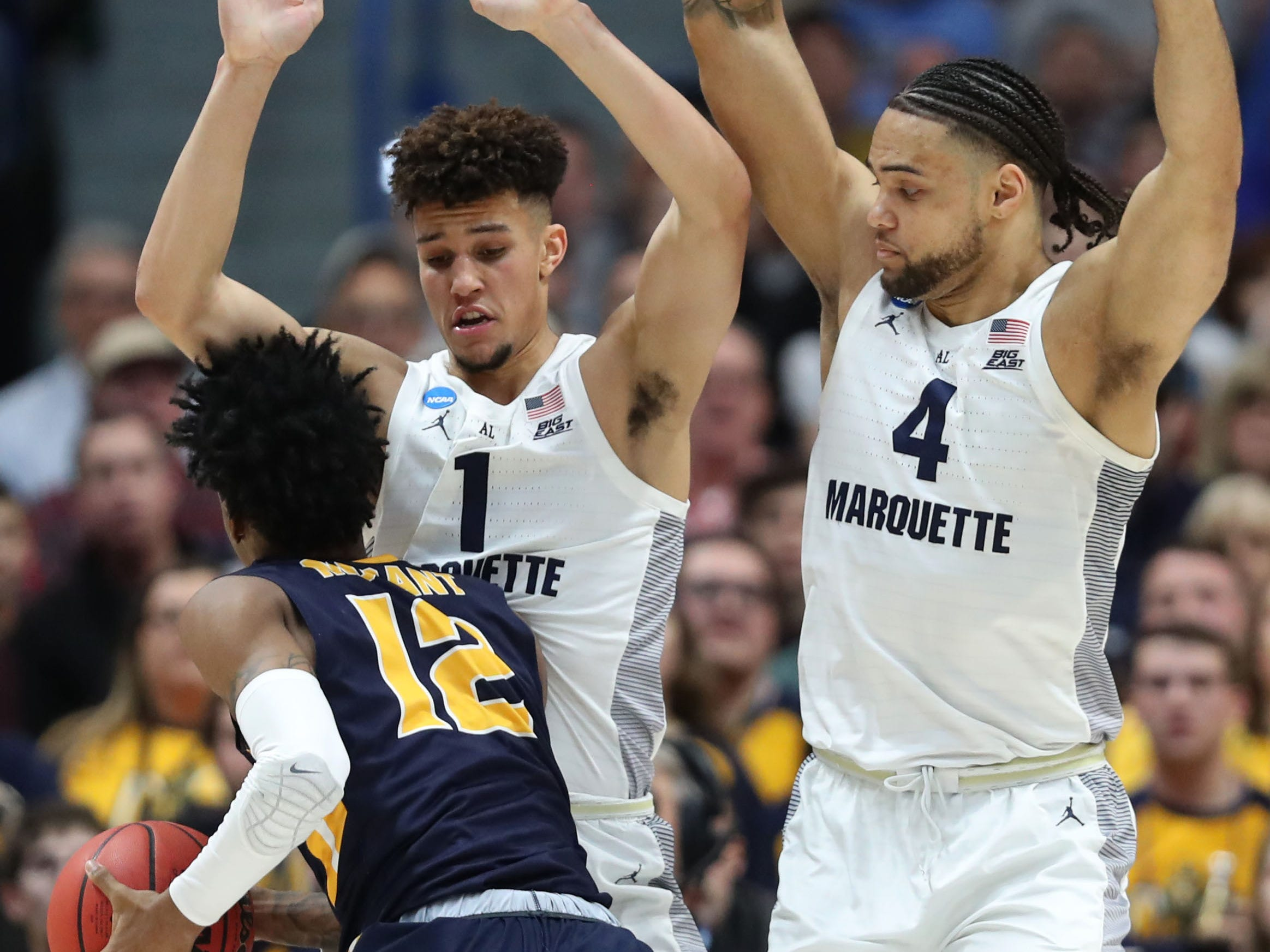 Marquette forward Brendan Bailey and Theo John attempt to prevent Murray State's Ja Morant from getting to the basket.
