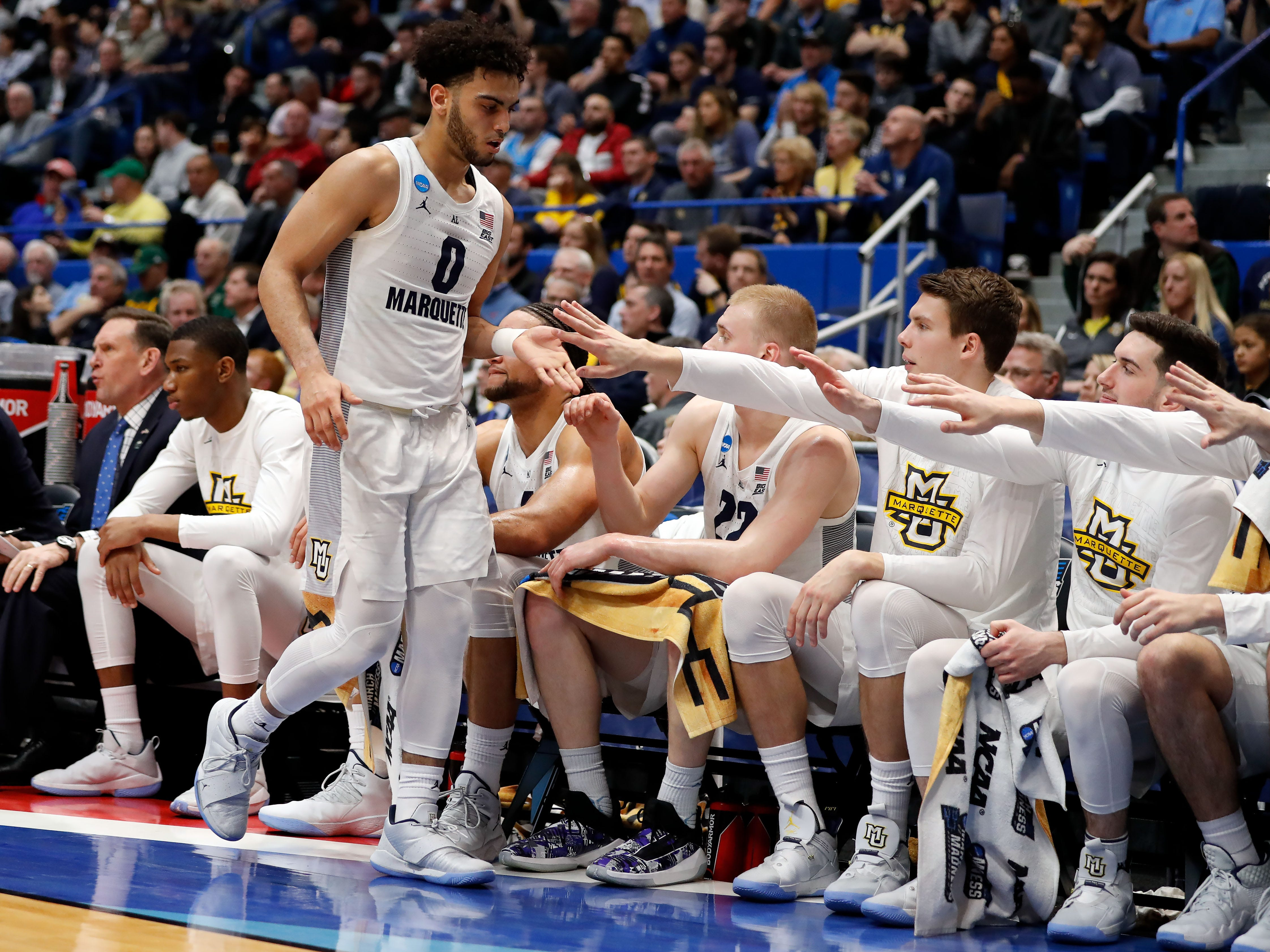Golden Eagles guard Markus Howard high fives his teammates as he leaves the game against Murray State for a short break during the first half.