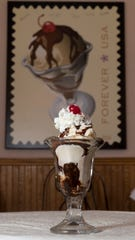 An ice cream sundae is shown in front of a photo of a stamp commemorating the dessert on Sunday, March 3, 2019, at the Historic Washington House & Two Rivers Historical Museum in Two Rivers. The building houses a replica of Ed Berner's Ice Cream Parlor, commemorating the invention of the ice cream sundae at the parlor in 1881. At least two other cities claim the title as well.