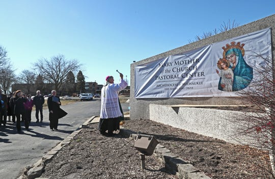 Milwaukee Archbishop Jerome Listecki blesses the sign outside the Archdiocese of Milwaukee's headquarters complex on Friday. The archdiocese renamed the complex the Mary Mother of the Church Pastoral Center days after removing the name of former Archbishop William E. Cousins for his role in the coverup of sex crimes against children.