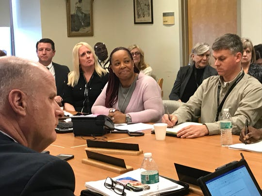 With Morris County Sheriff and board member James Gannon in the foreground, CEO Tomika Carter, center, listens to speakers during the public portion of the Greystone Park Psychiatric Hospital Board of Trustees meeting in Parsippany. March 21, 2019.