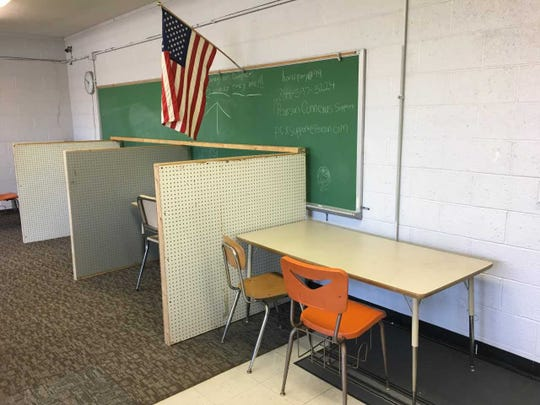 Cubicles made of pegboards and two-by-fours separate students at Delaware Christian Academy.