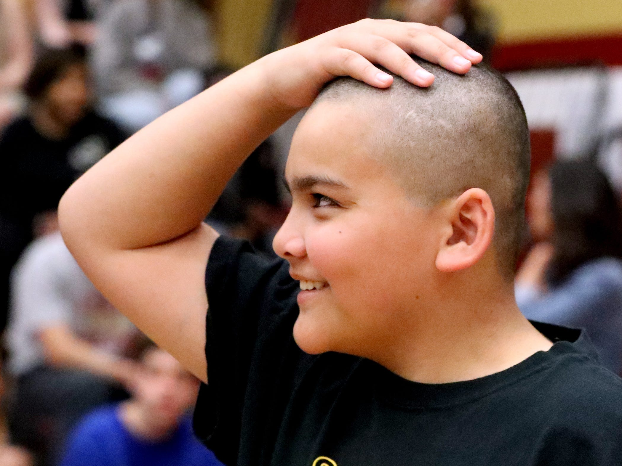 Kilin Wilson, 13, feels his head after he had it shaved during Riverdale High School's sixth annual Brave the Shave fundraiser to benefit St. Baldrick's Foundation on Thursday, March 21, 2019. The organization raises funds and awareness for childhood cancer.