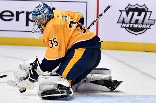 Predators goaltender Pekka Rinne (35) deflects a Penguins shot on goal during the second period at Bridgestone Arena Thursday, March 21, 2019 in Nashville, Tenn.