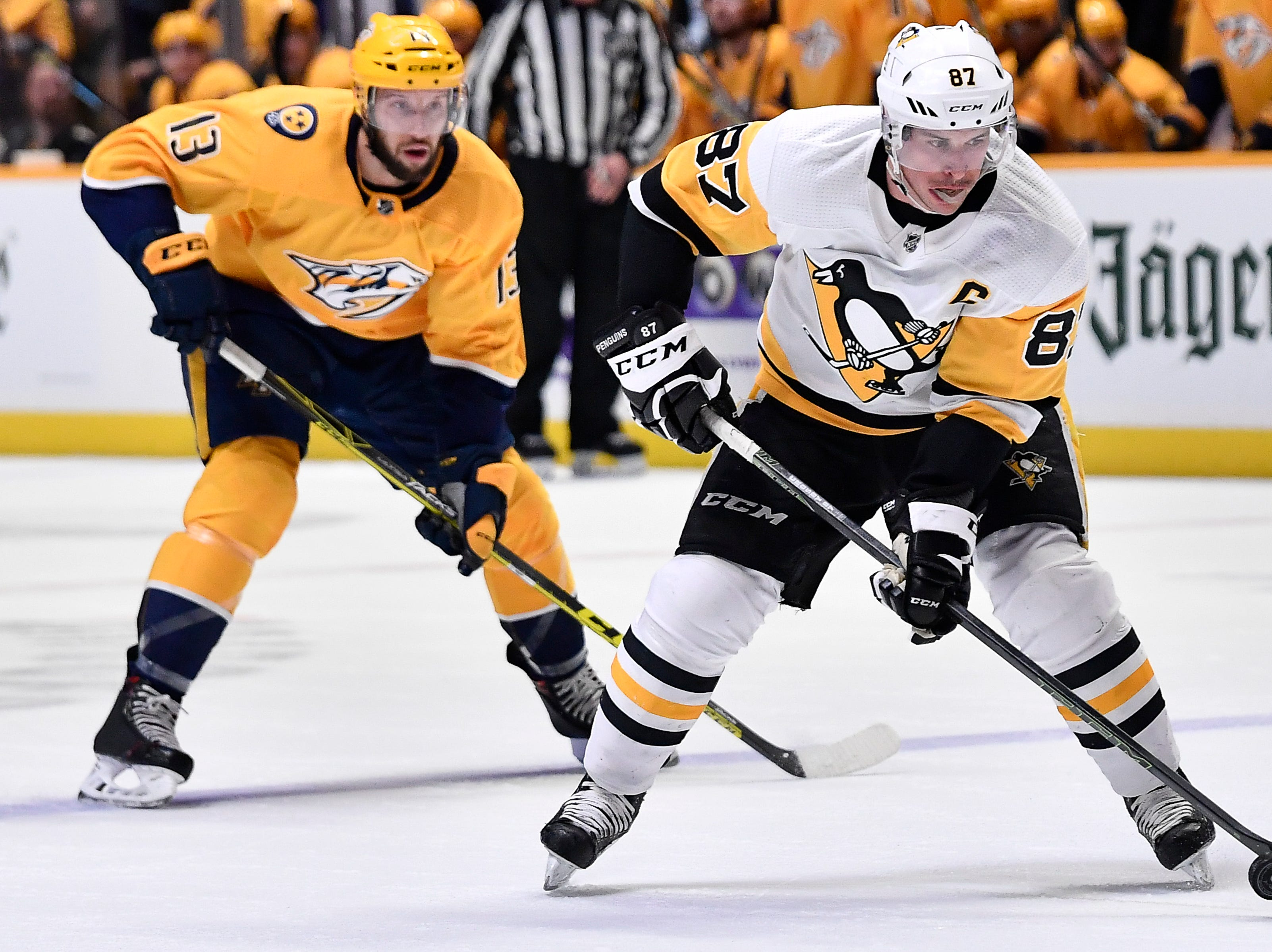 Penguins center Sidney Crosby (87) speeds past Predators center Nick Bonino (13) during the second period at Bridgestone Arena Thursday, March 21, 2019 in Nashville, Tenn.