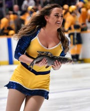 A Predators ice girl skates off the ice with a catfish before the first period of their game against the Penguins at Bridgestone Arena Thursday, March 21, 2019 in Nashville, Tenn.
