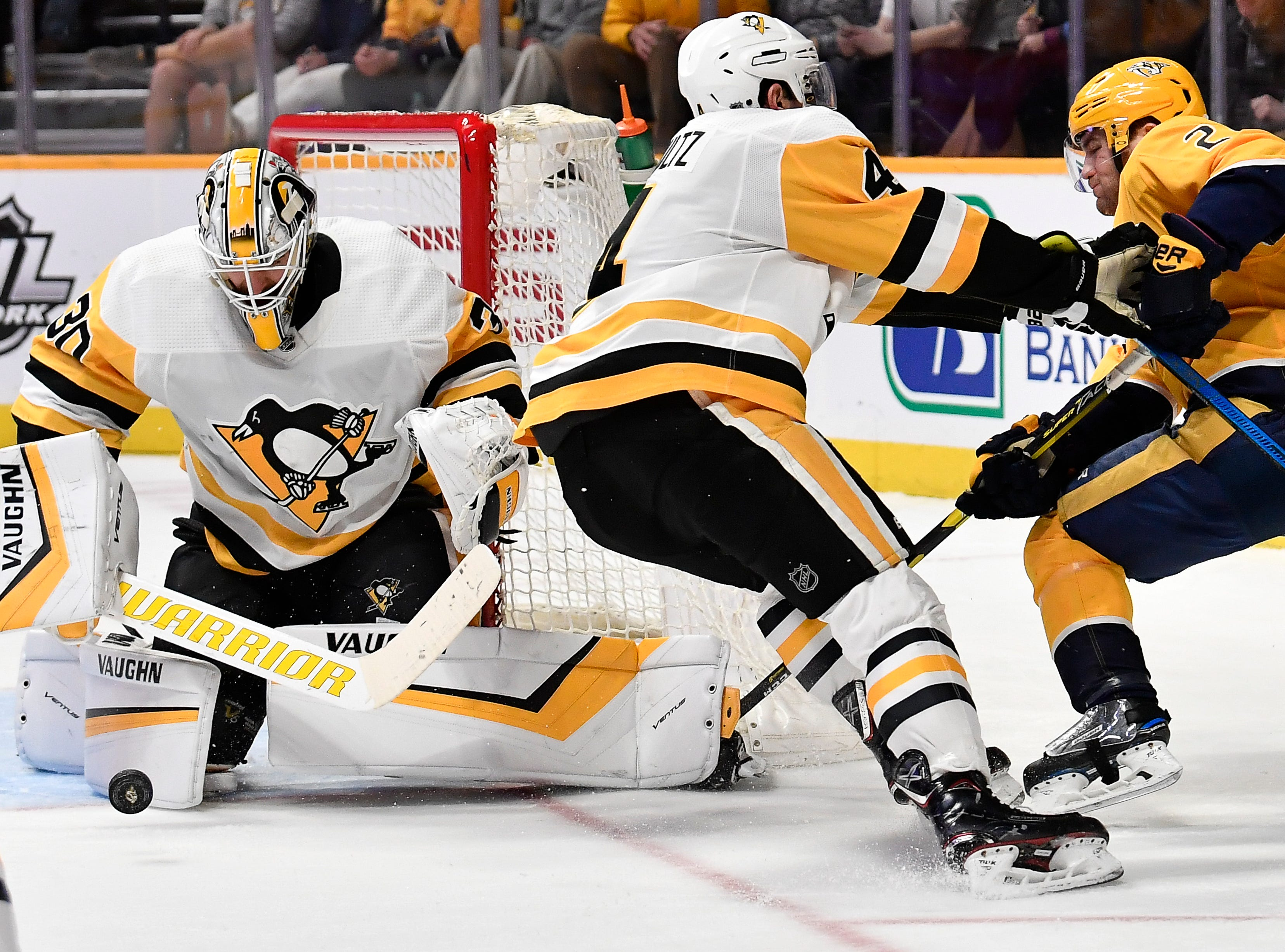 Penguins goaltender Matt Murray (30) blocks a Predators shot on goal as Penguins defenseman Justin Schultz (4) pushes Predators center Rocco Grimaldi (23) away during the third period at Bridgestone Arena Thursday, March 21, 2019 in Nashville, Tenn.