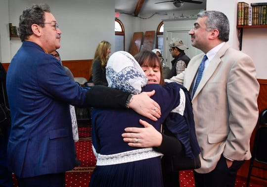 Rabbi Mark Schiftan shakes hands with Umit Gunebir as Rabbi Shana Goldstein Mackler hugs the Director of the Islamic Center of Nashville on Friday.