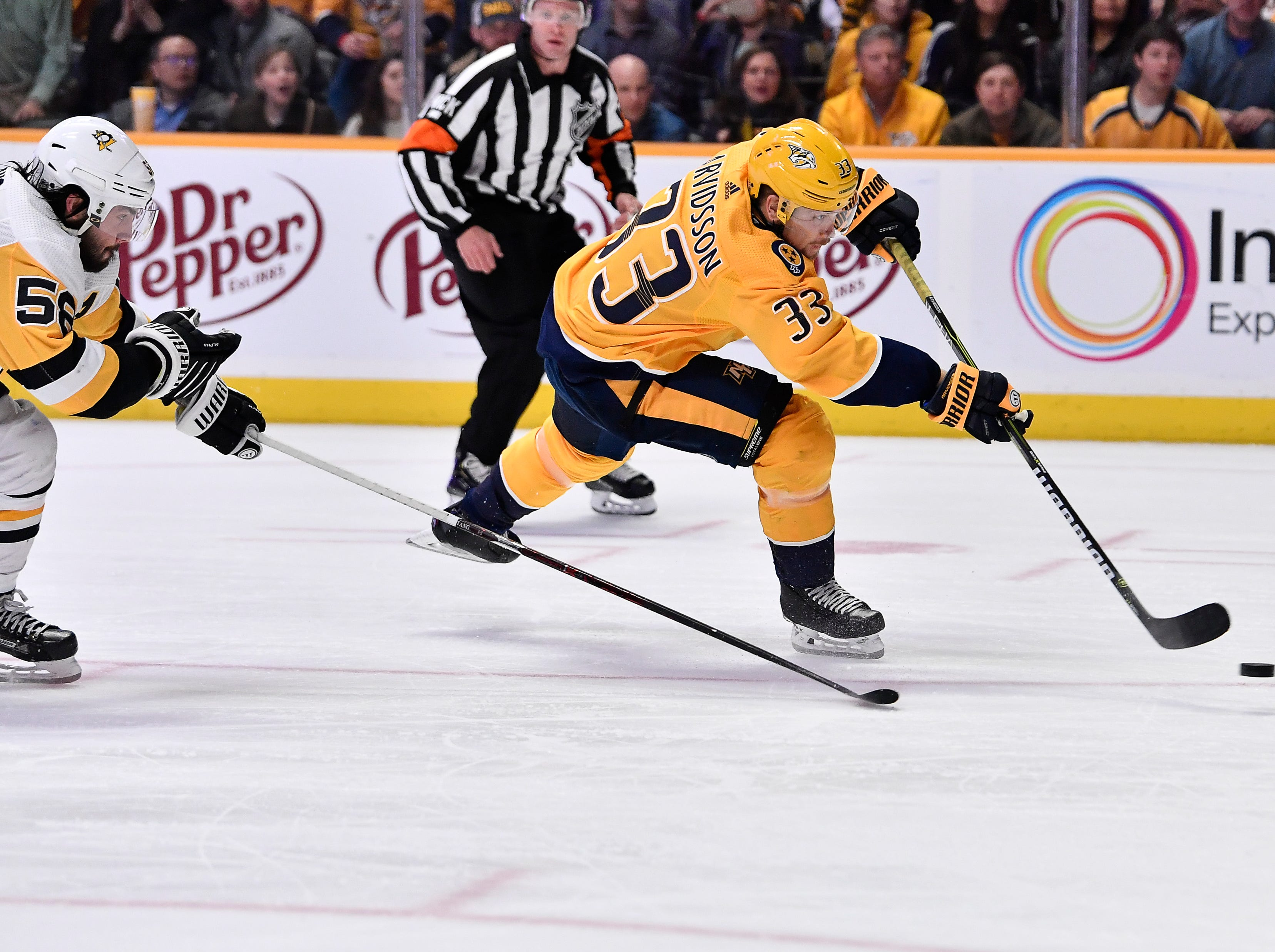 Predators right wing Viktor Arvidsson (33) shoots the puck past Penguins defenseman Kris Letang (58) during the third period at Bridgestone Arena Thursday, March 21, 2019 in Nashville, Tenn.
