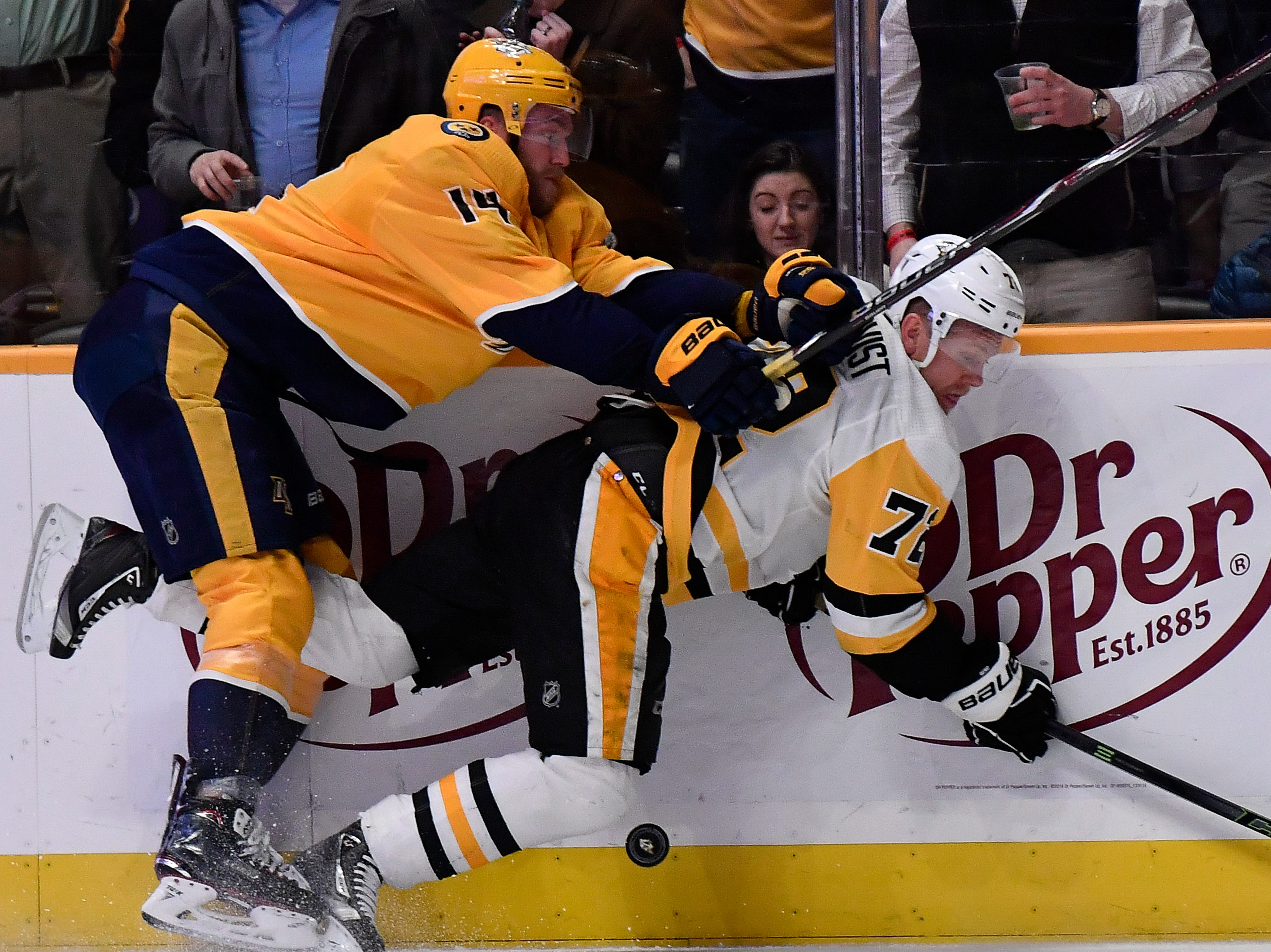 Predators defenseman Mattias Ekholm (14) pounds Penguins right wing Patric Hornqvist (72) into the ice during the third period at Bridgestone Arena Thursday, March 21, 2019 in Nashville, Tenn.