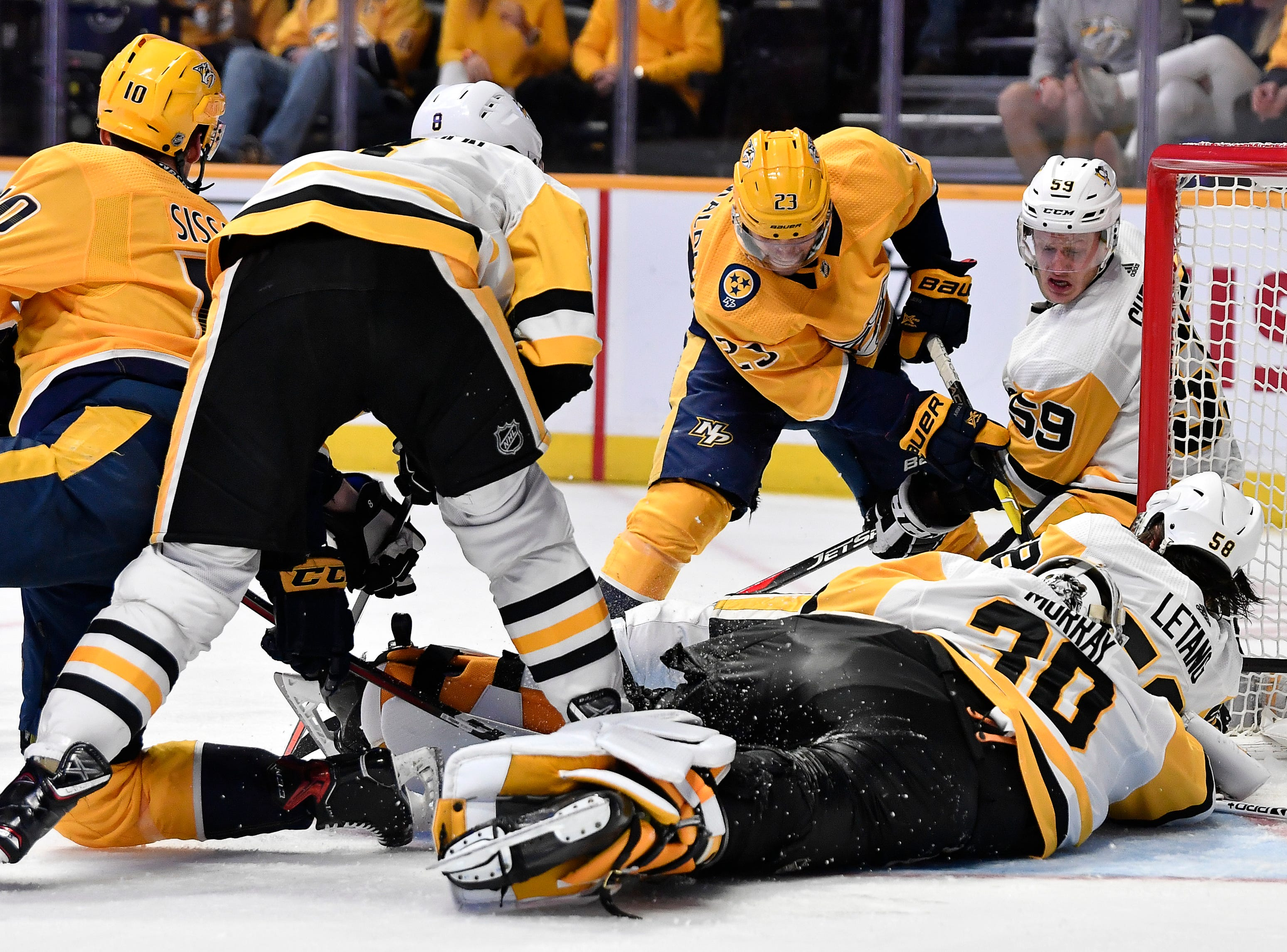Penguins goaltender Matt Murray (30) and left wing Jake Guentzel (59) defend the goal against the Predators during the third period at Bridgestone Arena Thursday, March 21, 2019 in Nashville, Tenn.