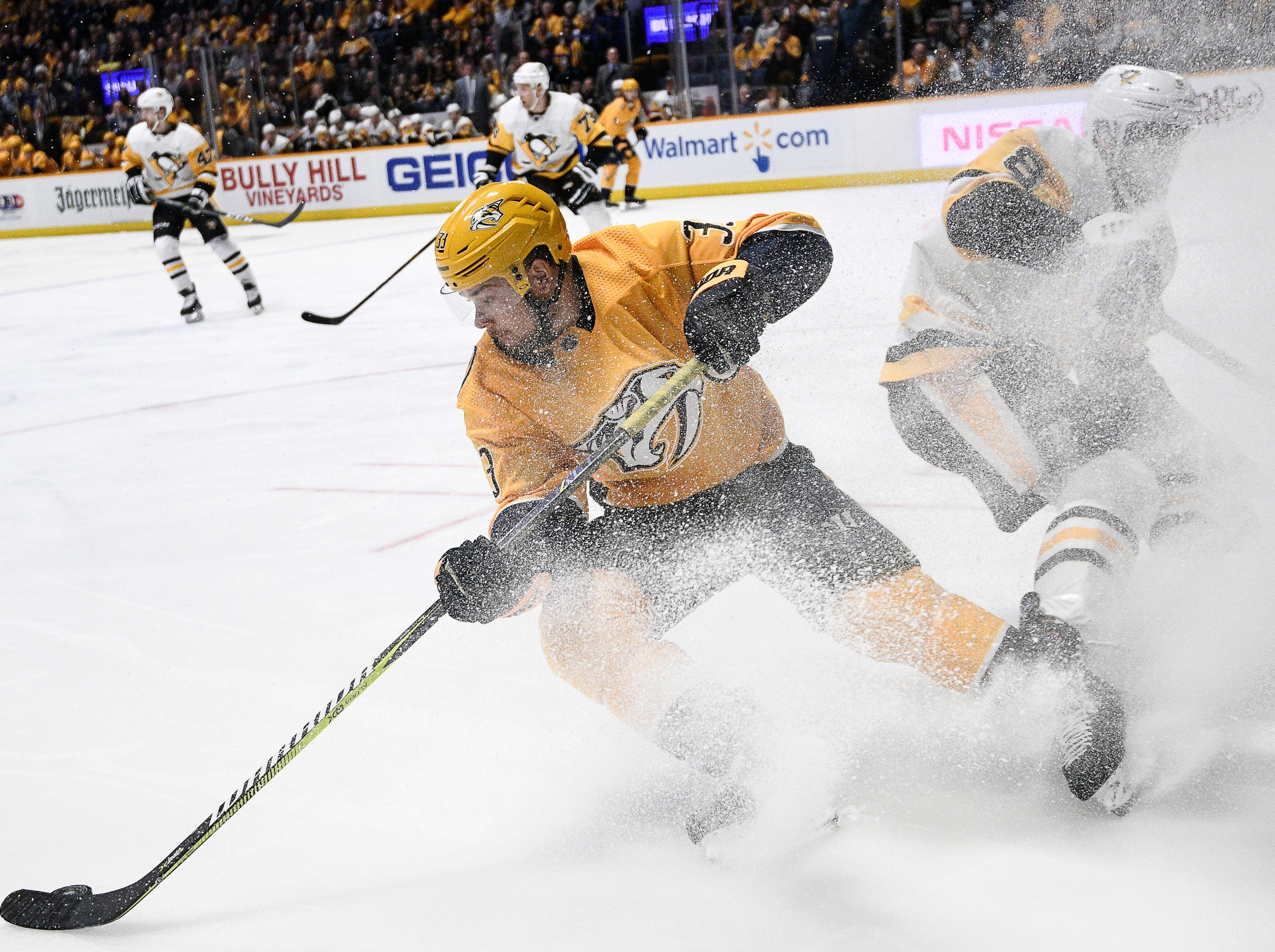 Predators right wing Viktor Arvidsson (33) stops fast to gather a puck before Penguins defenseman Brian Dumoulin (8) during the first period at Bridgestone Arena Thursday, March 21, 2019 in Nashville, Tenn.