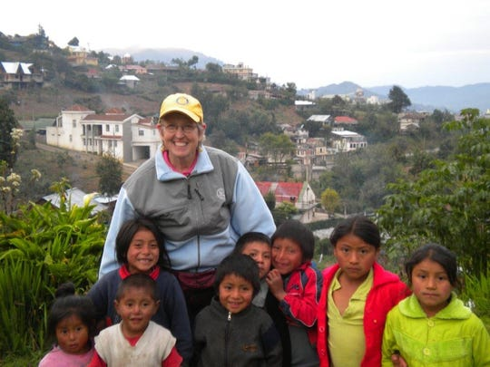 Sally Smith poses for a photo with children from the village of SataqNa during one of her trips to Guatemala.