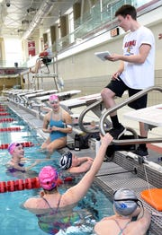 Granville freshman Elizabeth Hedger (center) and Pau Hana teammates Gabrielle Brust, Hannah Hardin, Caroline Holmes, and Riley Bunstine listen as assistant coach Joel Roth gives them their next exercise during a practice on Monday, March 18, 2019 at Denison University's Trumbull Aquatic Center. Hedger, who also swims for the Blue Aces, will be competing in April in Indianapolis as a part of the World Para SwimmingÕs 2019 World Series.