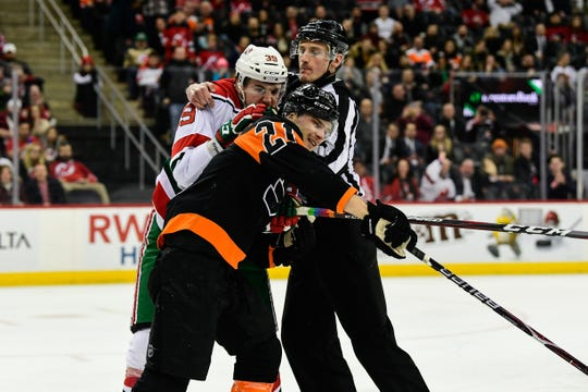 New Jersey Devils right wing Kurtis Gabriel (39) has something to say to  Philadelphia Flyers center Scott Laughton (21) during the third period at Prudential Center on March 1, 2019. .