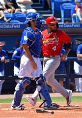Mar 22, 2019; Port St. Lucie, FL, USA; St. Louis Cardinals catcher Yadier Molina (4) scores a run in front of New York Mets catcher Travis d'Arnaud (18) during a spring training game at First Data Field.