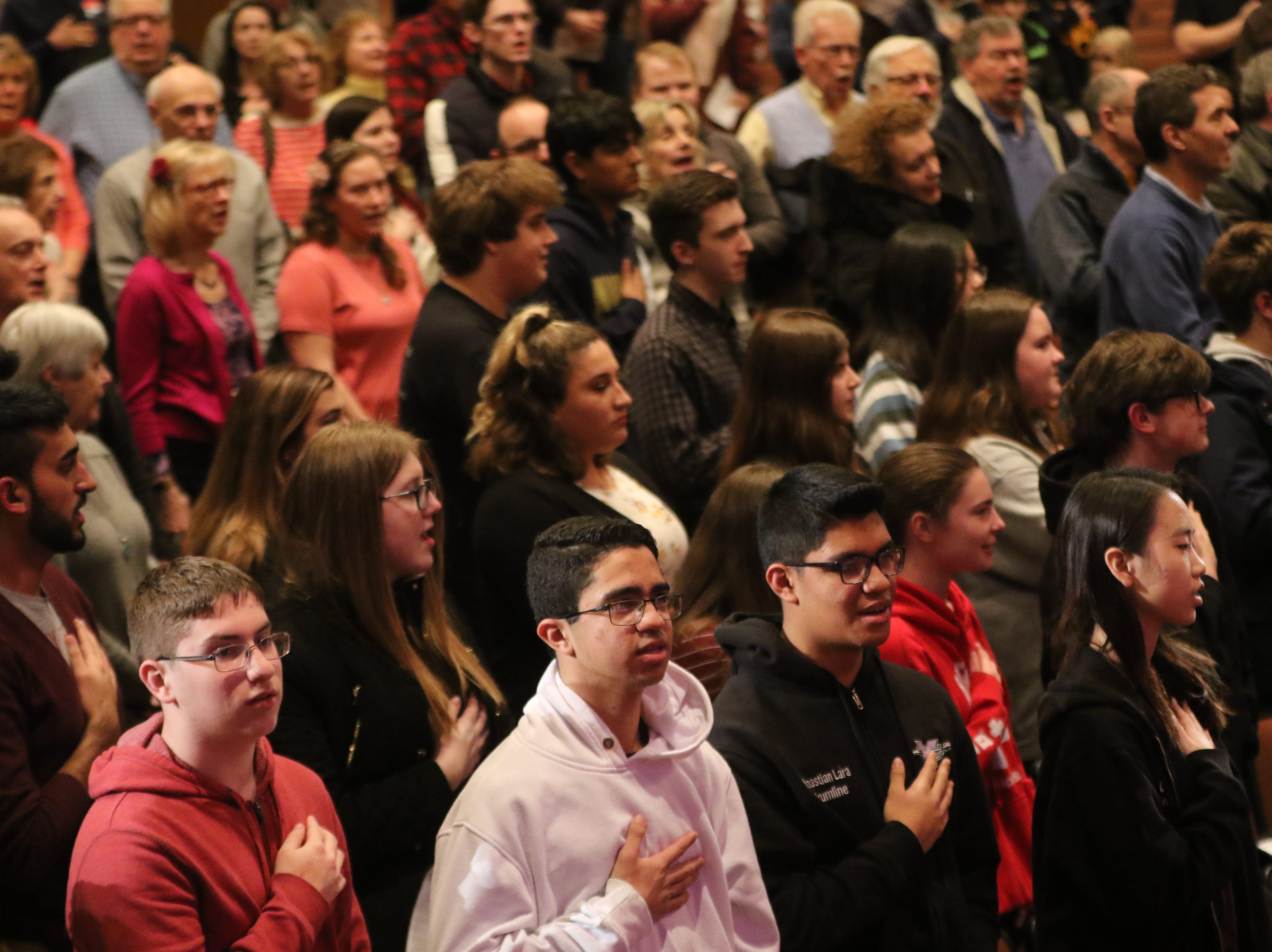 Concert-goers stand for 'The Star-Spangled Banner', in Wayne.  The United States Army Jazz Ambassadors Field Band performed at Wayne Hills High School, Thursday, March 21, 2019.  This was the eleventh day of their tour, which lasts more than a month.